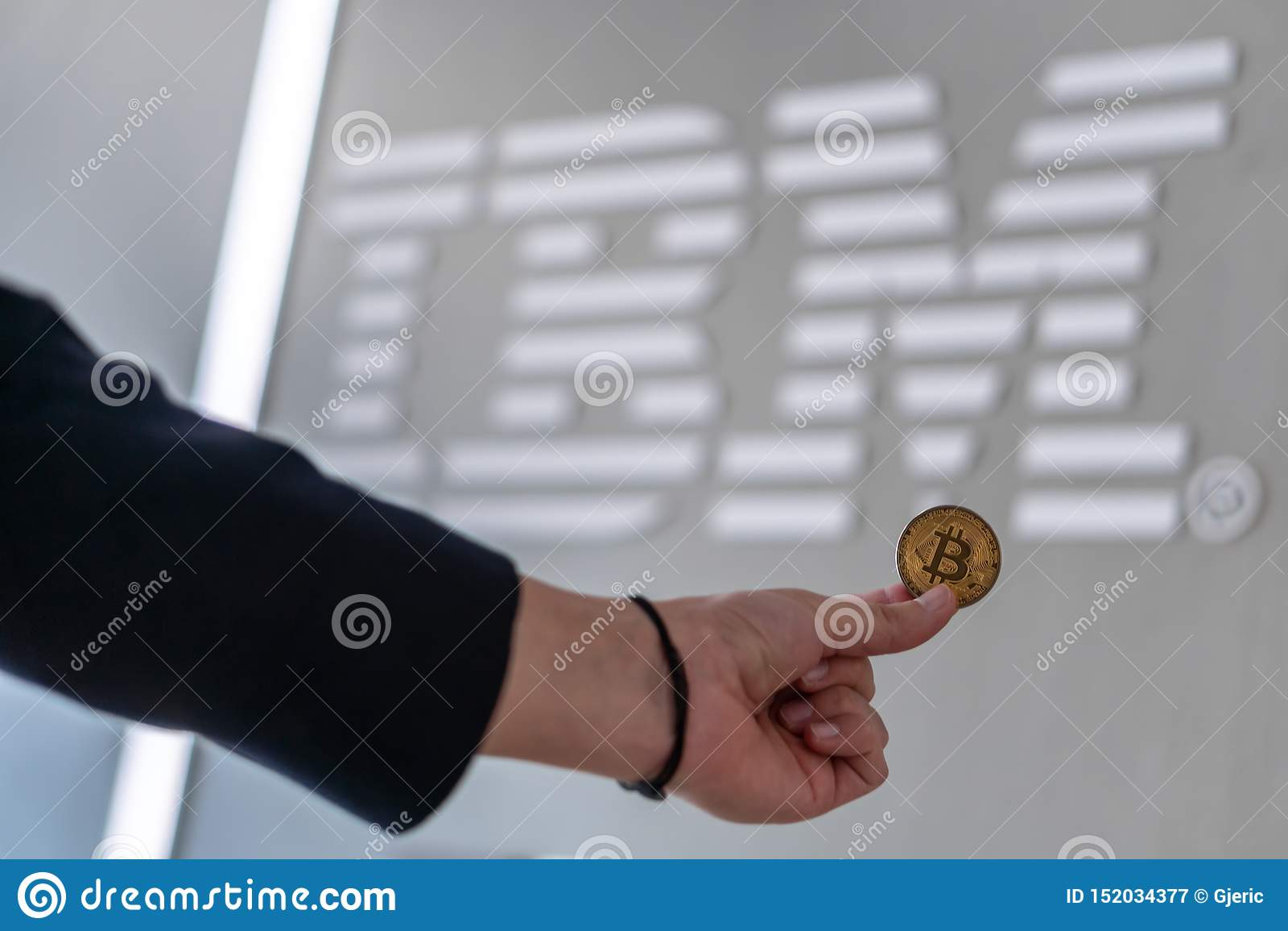 Бизнесмен держа монетку с логотипом IBM на экране ноутбука, Словению - 26-ое февраля 2019 Bitcoin