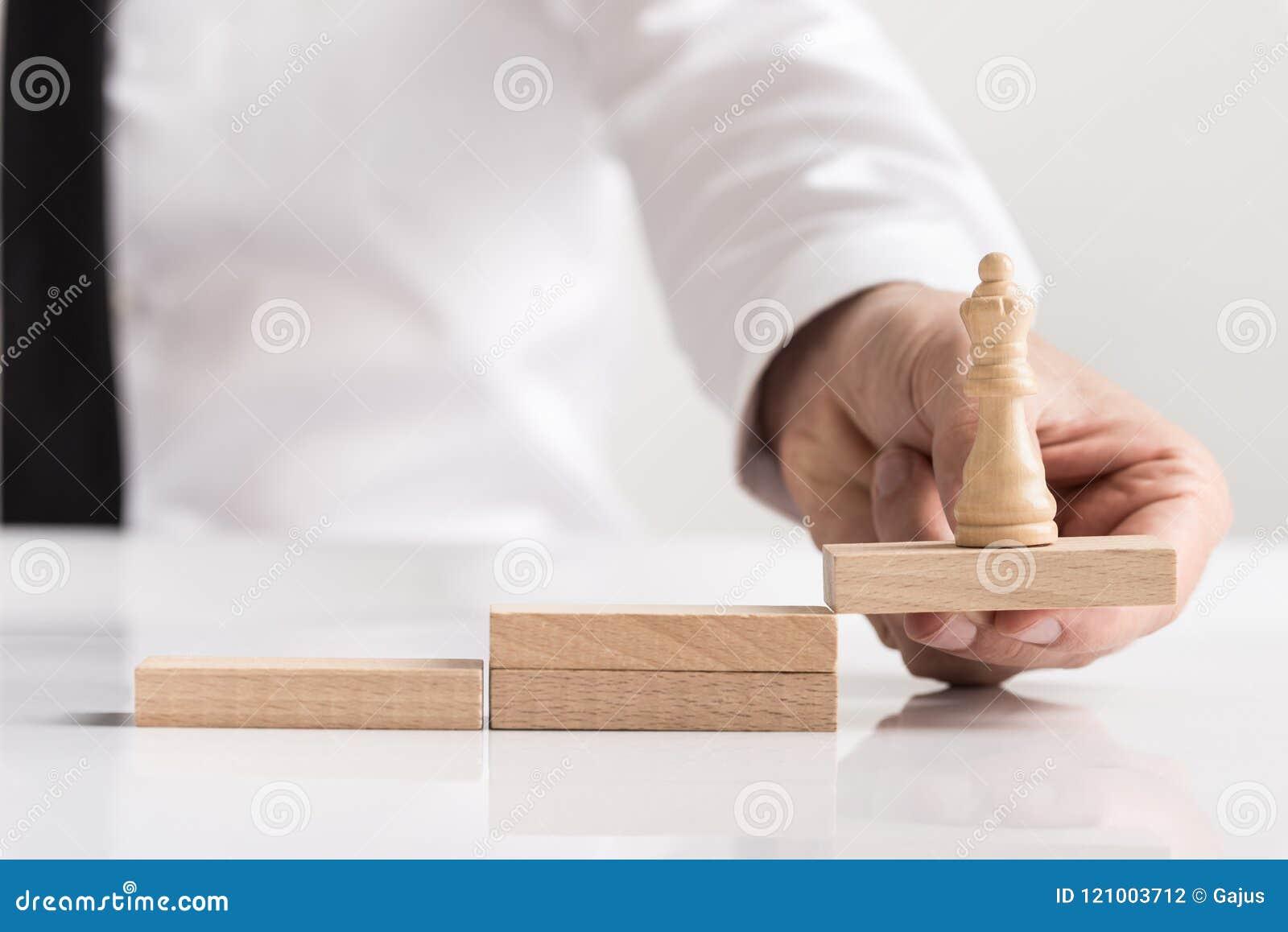 Бизнесмен держа шахматную фигуру ферзя на блоке