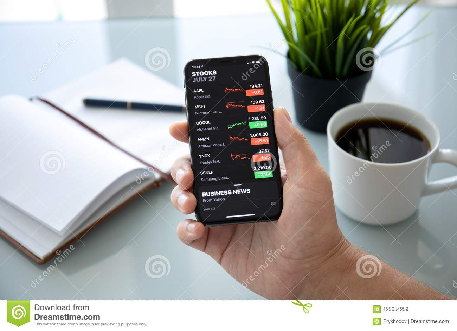 Бизнесмен держа iPhone x с запасами применения Яблока