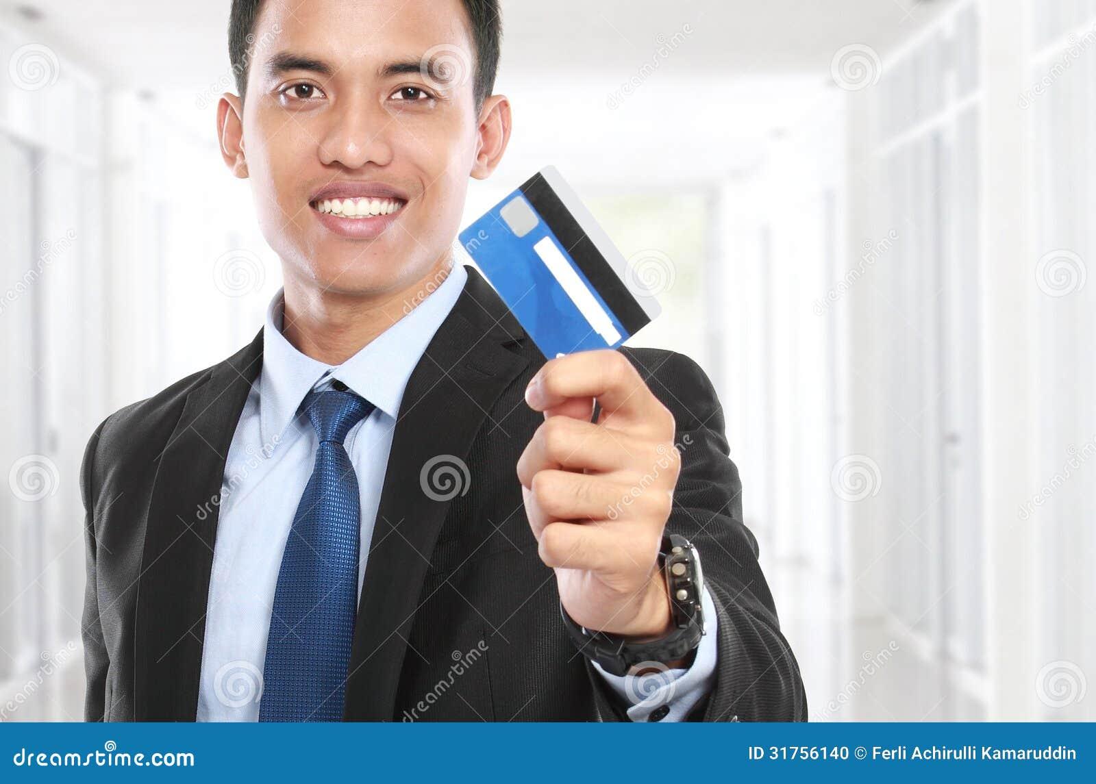 Бизнесмен держа кредитную карточку и улыбку