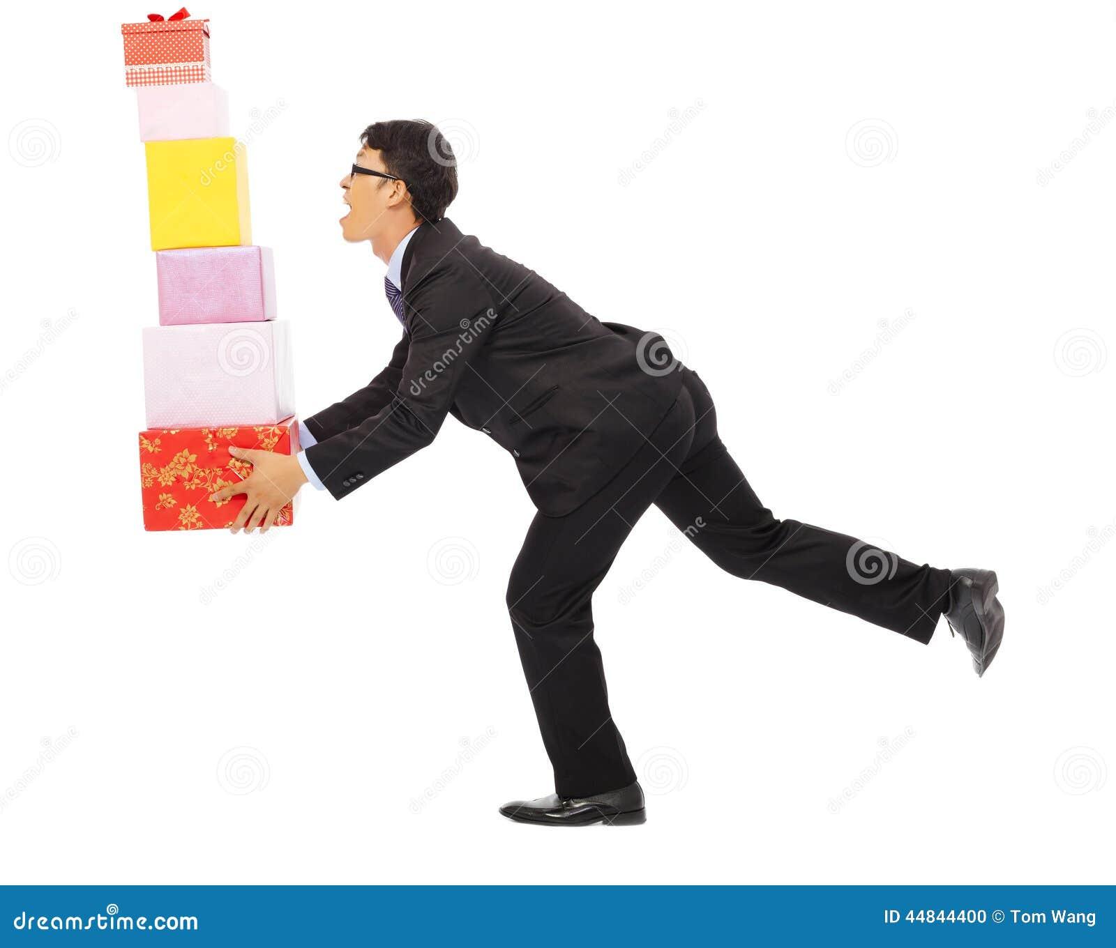 Бизнесмен держа некоторые подарочные коробки Изолировано на белизне