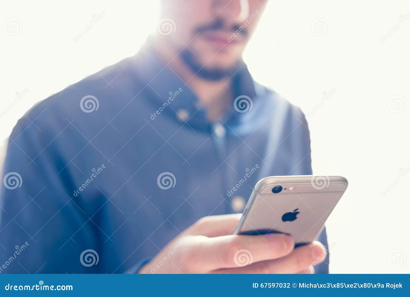 Бизнесмен держа новую сетчатку iPhone 6s Яблока