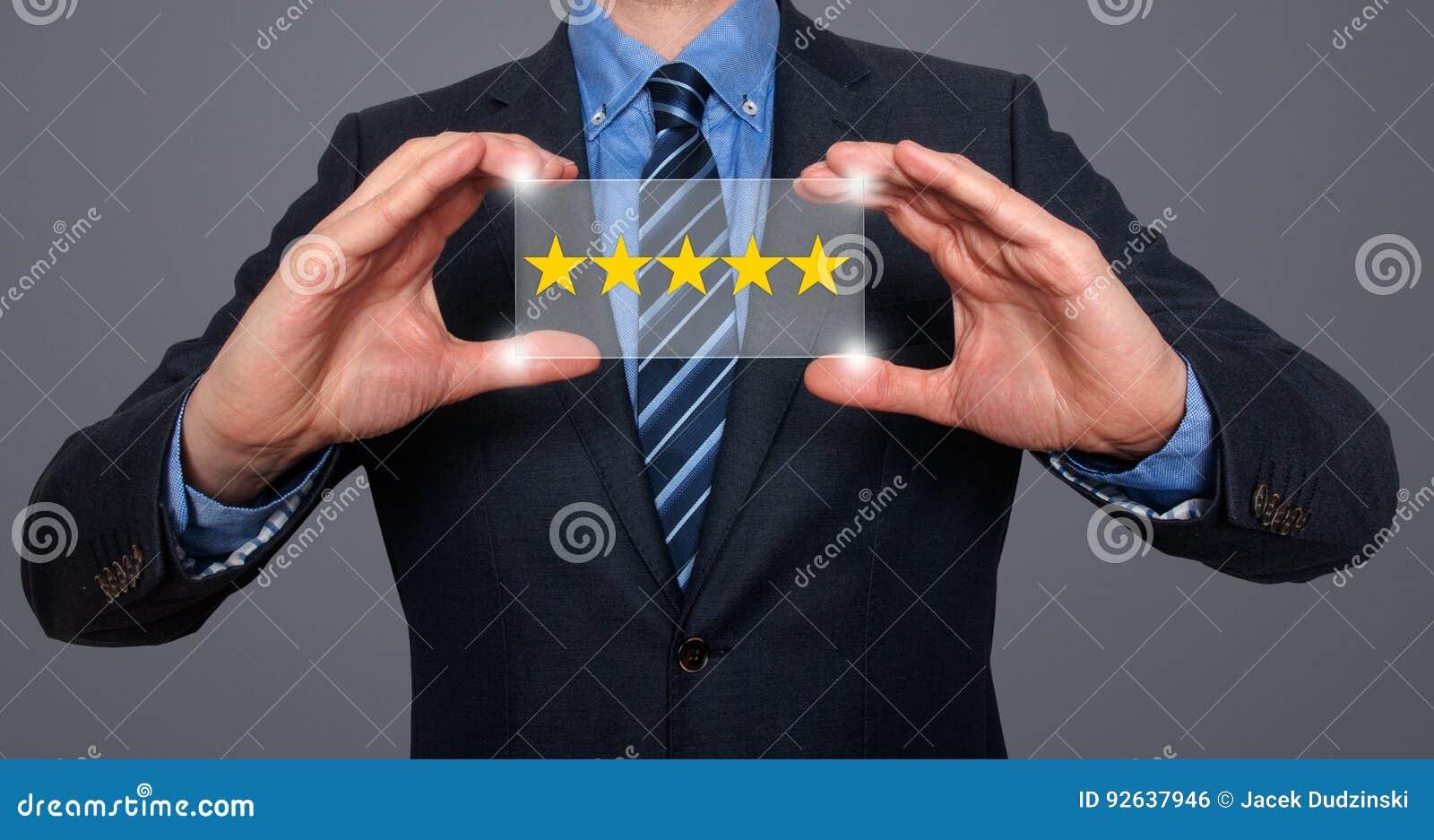 Бизнесмен держа оценку 5 звезд