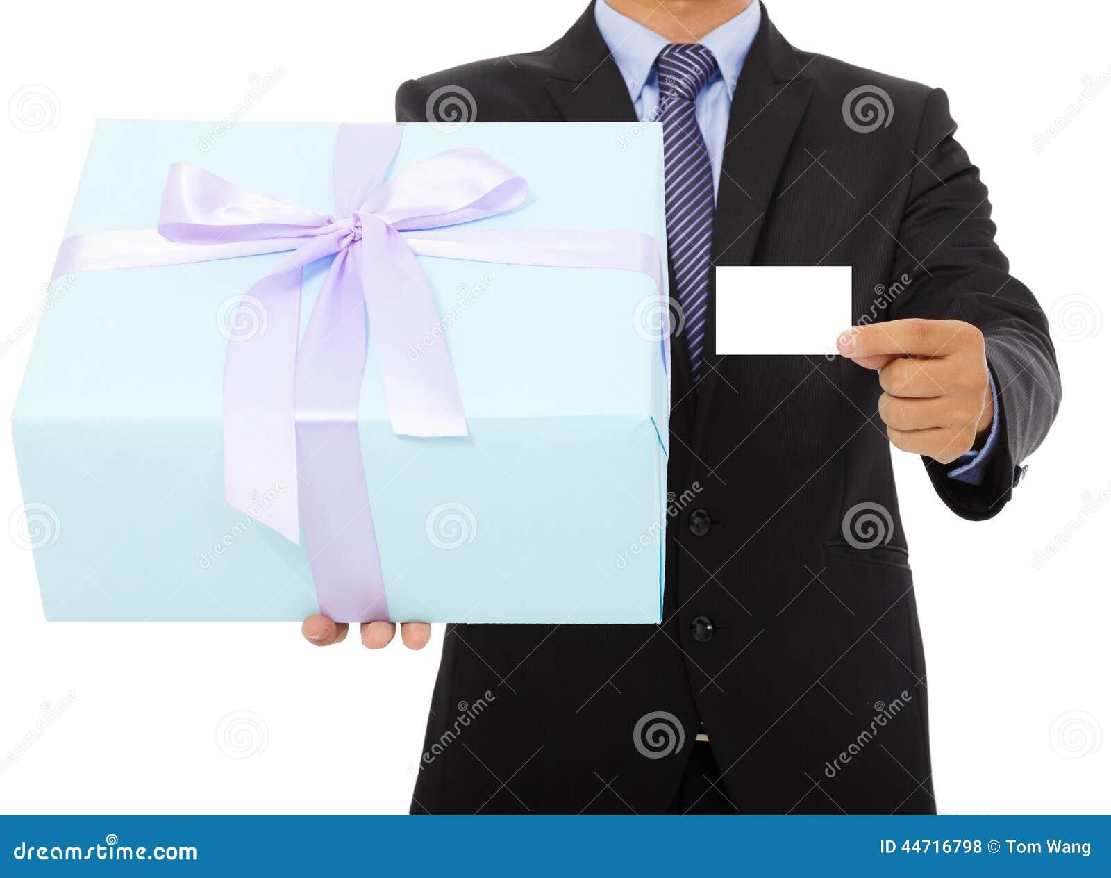 Бизнесмен держа подарочную коробку и карточку