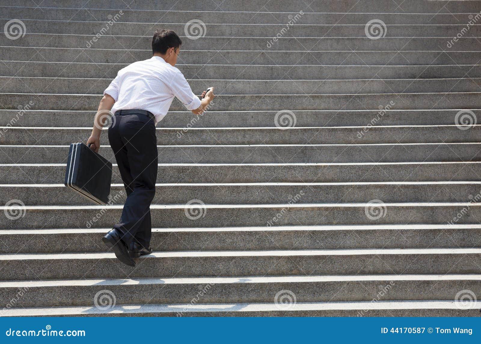 Бизнесмен держа чернь и в спешности для того чтобы побежать вверх на лестницах