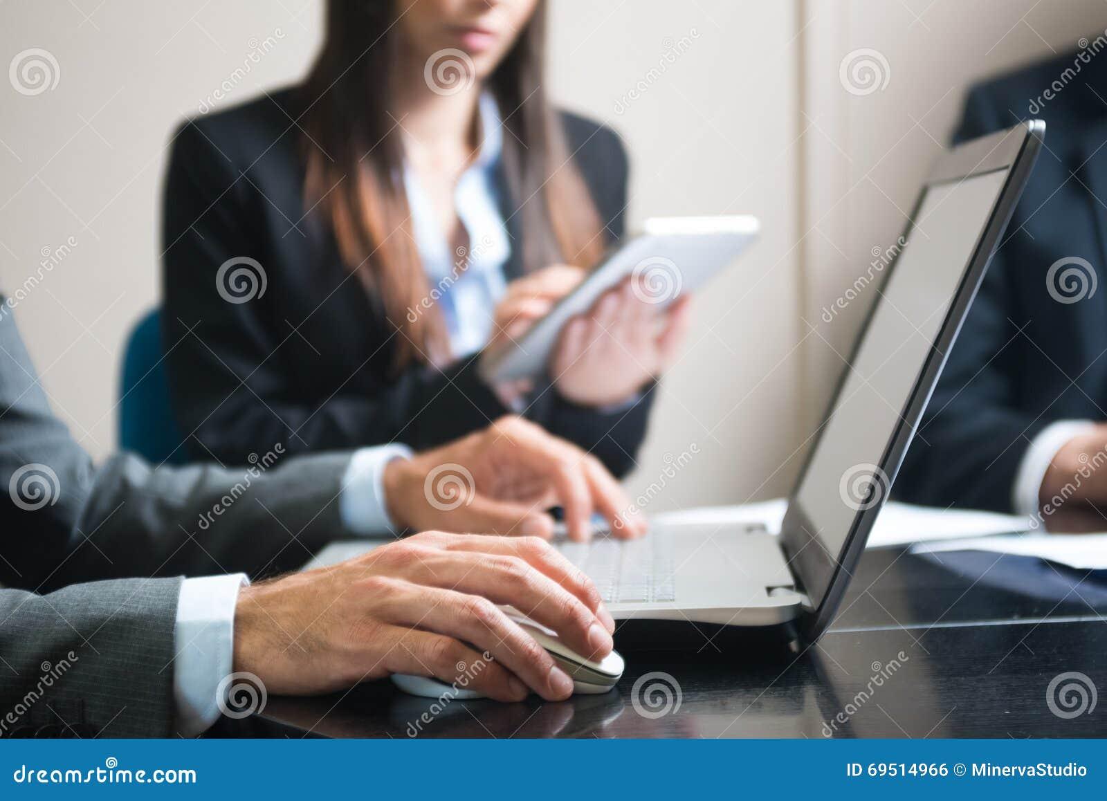 Бизнесмен используя его портативный компьютер во время встречи
