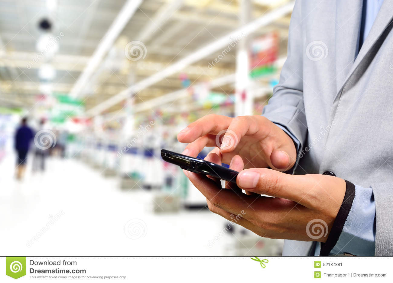Бизнесмен используя мобильный телефон пока ходящ по магазинам в супермаркете