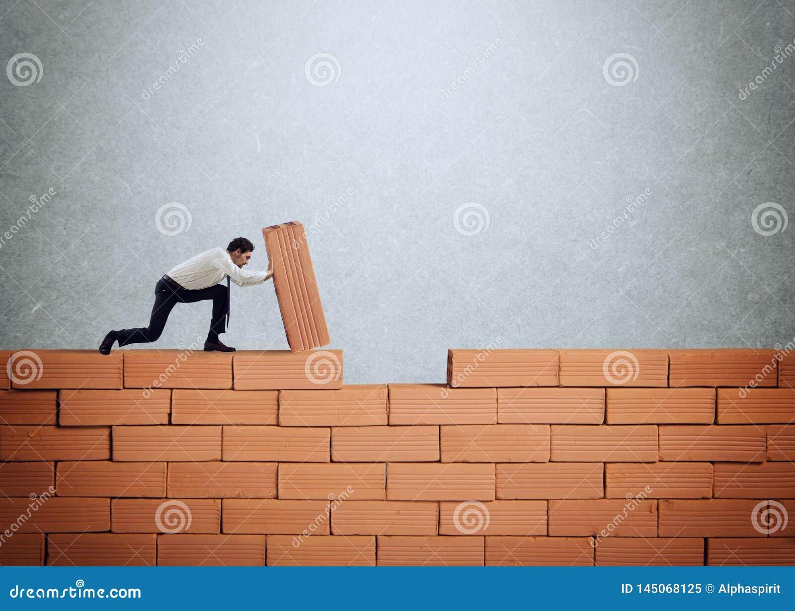Бизнесмен кладет кирпич для построения стены Концепция новых дела, партнерства, интеграции и запуска