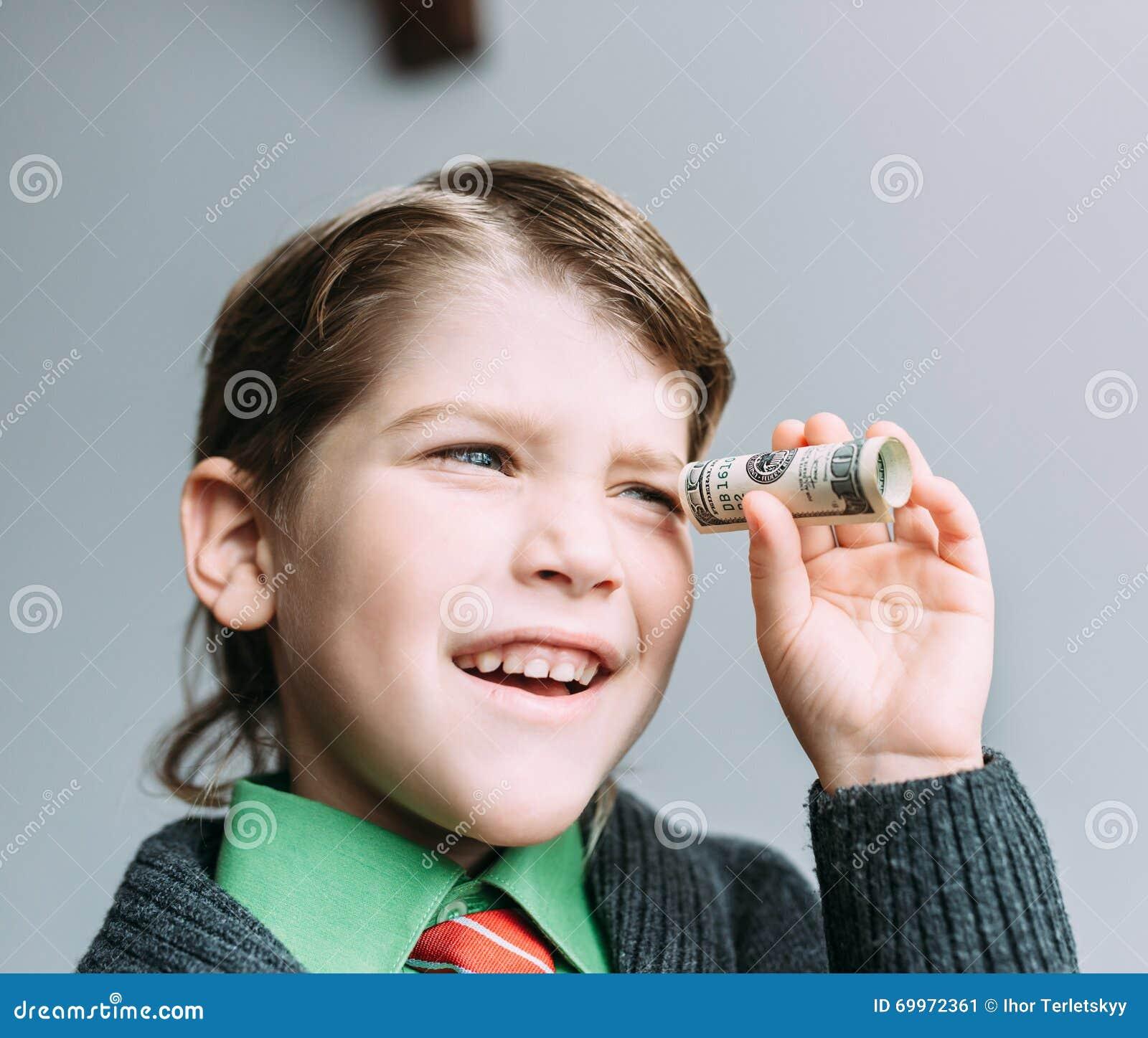 Бизнесмен мальчика смотрит через малую трубку от доллара