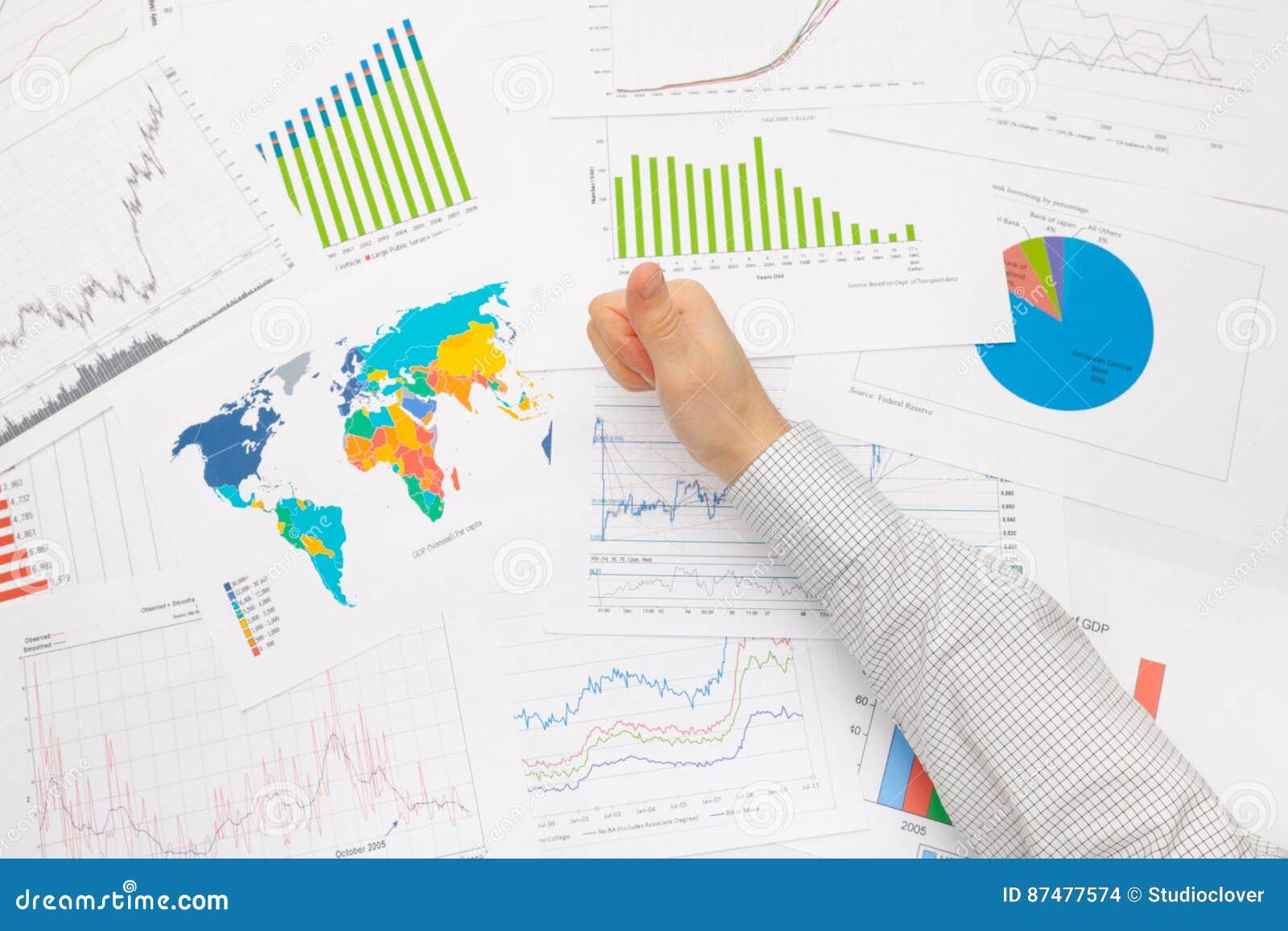 Бизнесмен на таблице при различные финансовые данные держа большой палец руки вверх