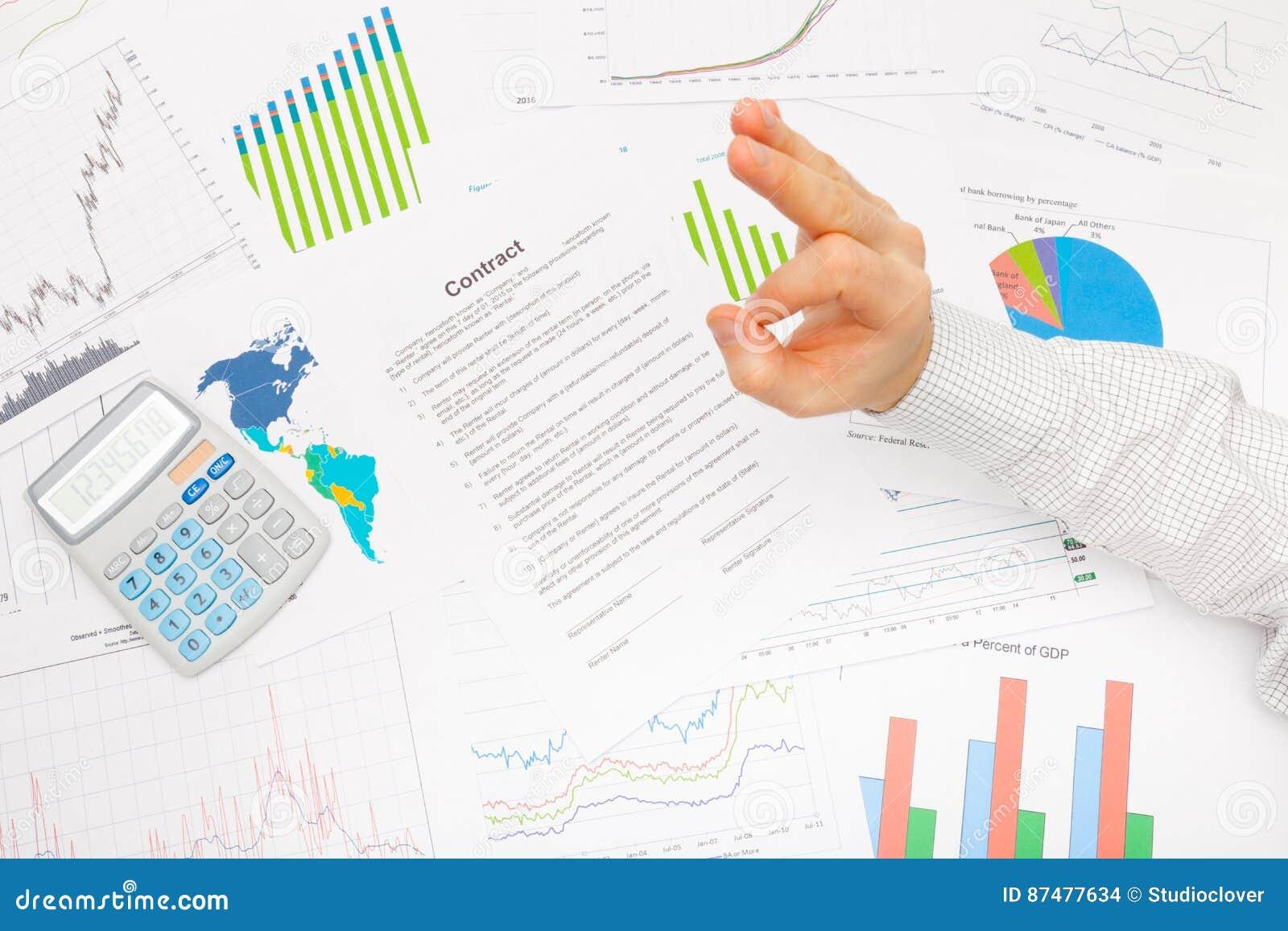 Бизнесмен на таблице при различные финансовые данные показывая знак - ОДОБРЕННЫЙ