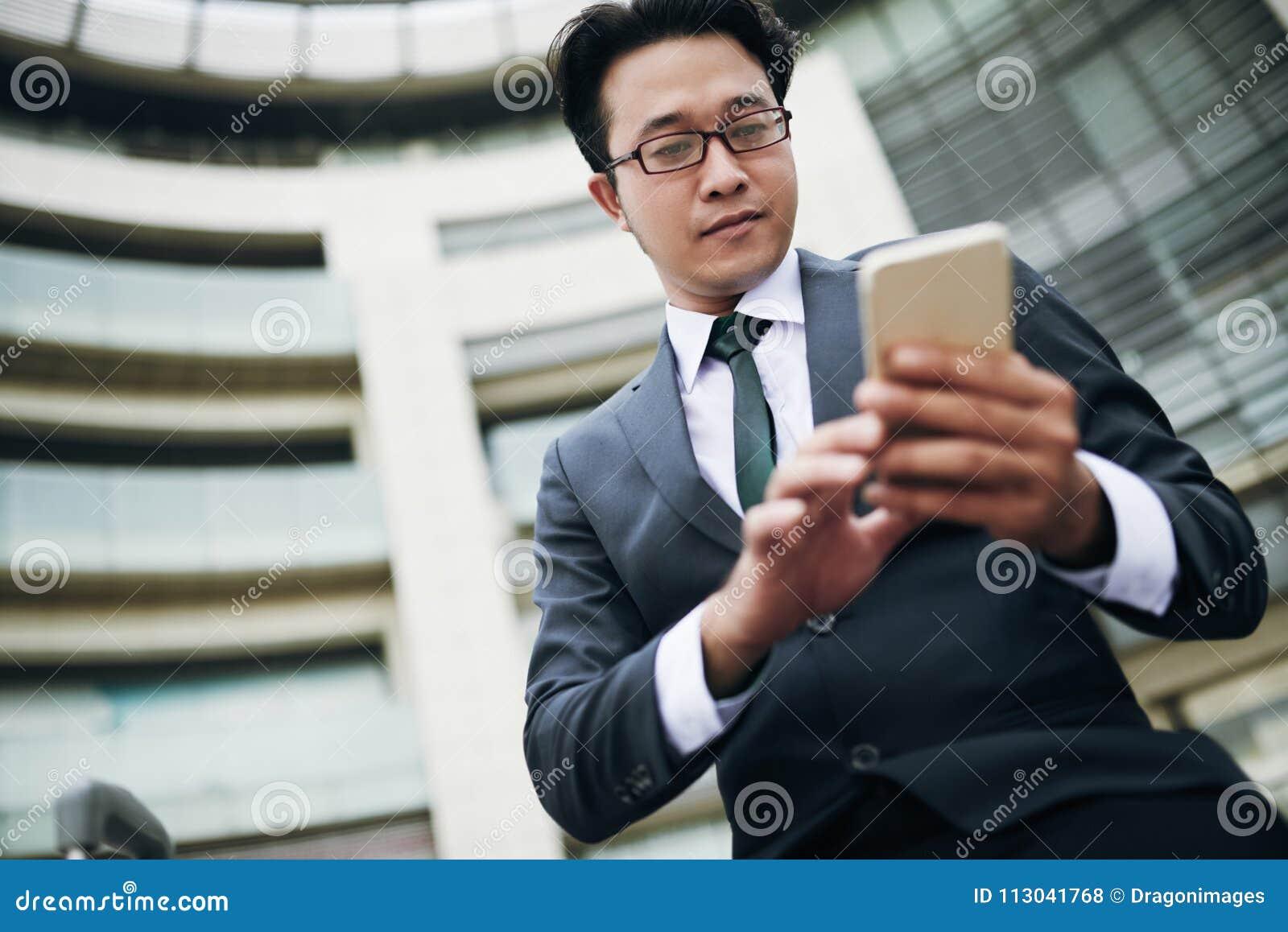 Бизнесмен отправляя СМС на smartphone