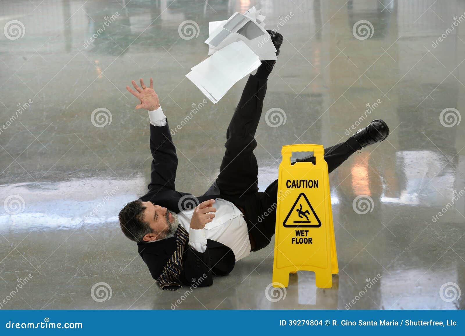 Бизнесмен падая на влажный пол