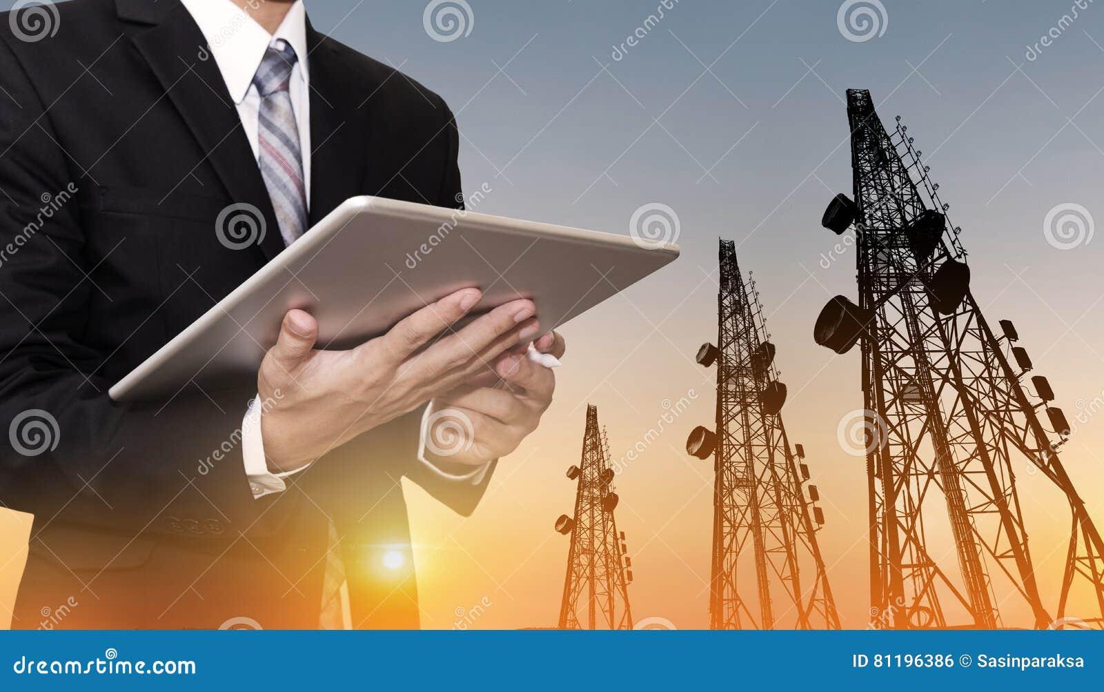 Бизнесмен работая на цифровой таблетке, с сетью телекоммуникаций спутниковой антенна-тарелки на башне радиосвязи в заходе солнца,