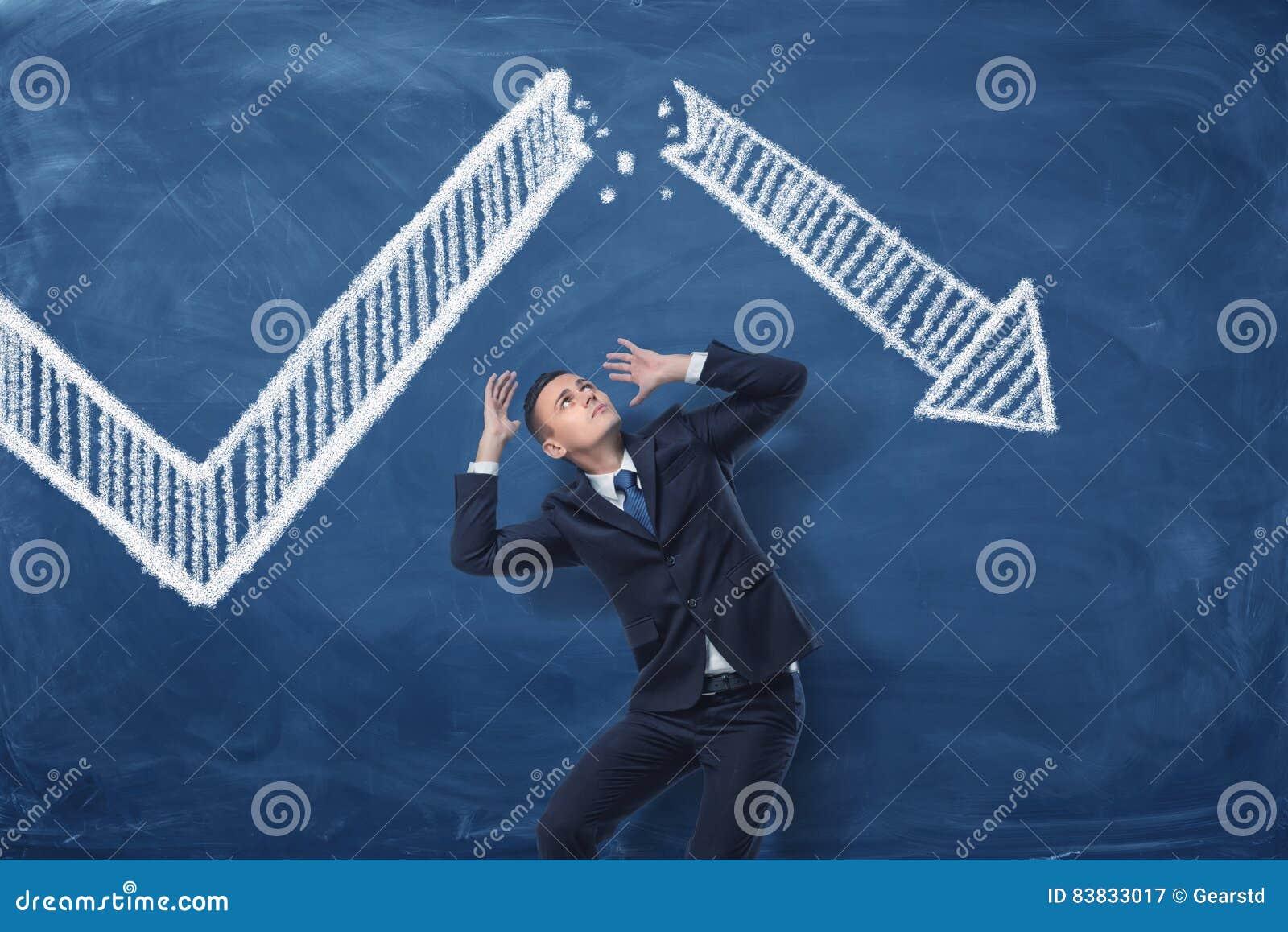 Бизнесмен сжимаясь на голубой предпосылке классн классного с чертежом мела белой стрелки статистики сломанной в половине