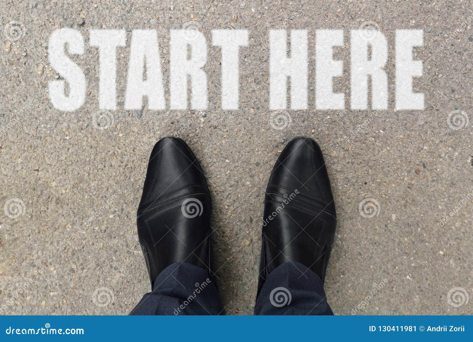 Бизнесмен смотрит вниз на его ногах на конкретном поле с письмами НАЧАЛА ЗДЕСЬ покрашенными на поверхности Изображение взгляда св