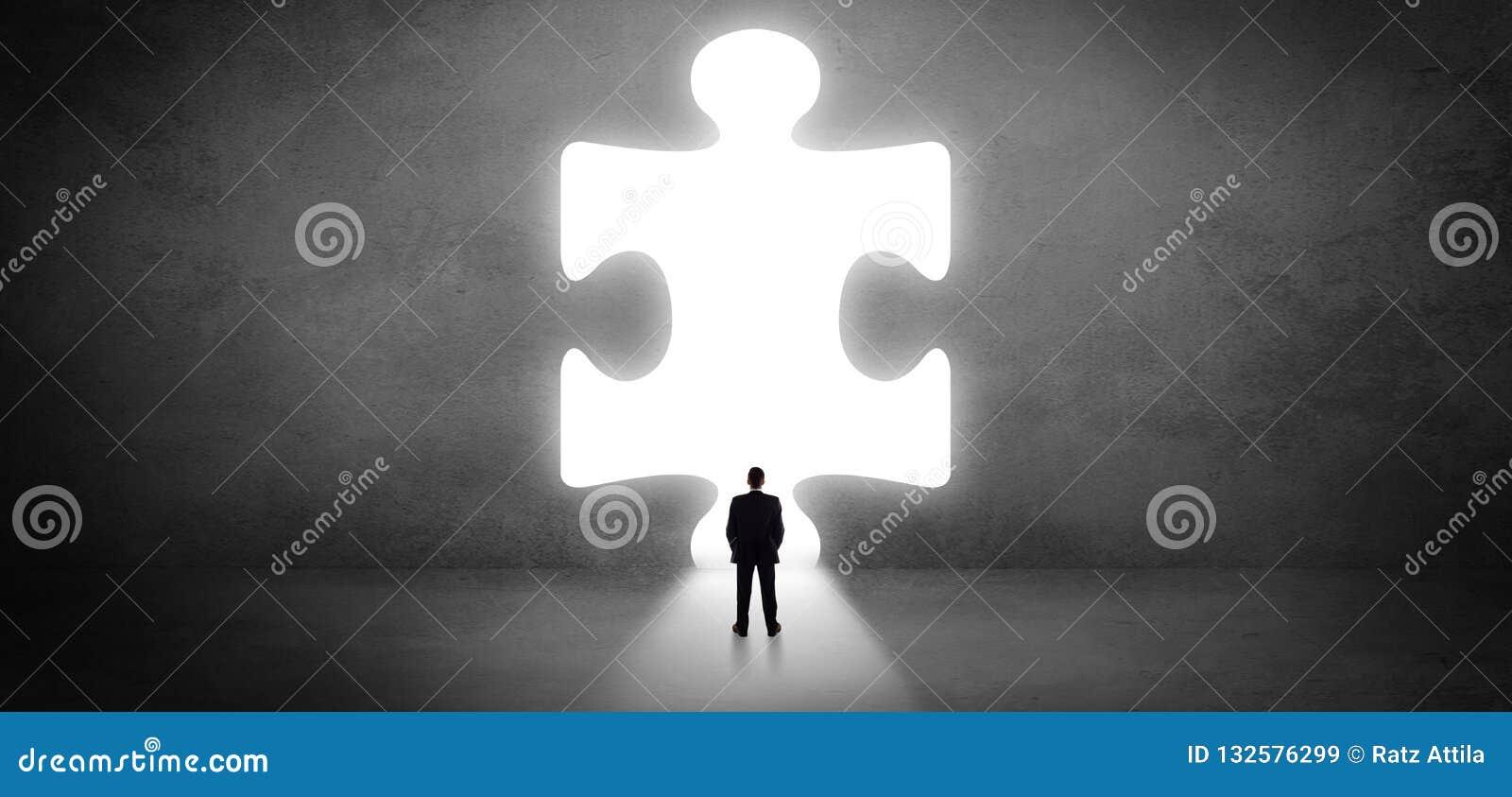 Бизнесмен стоя перед большой частью головоломки