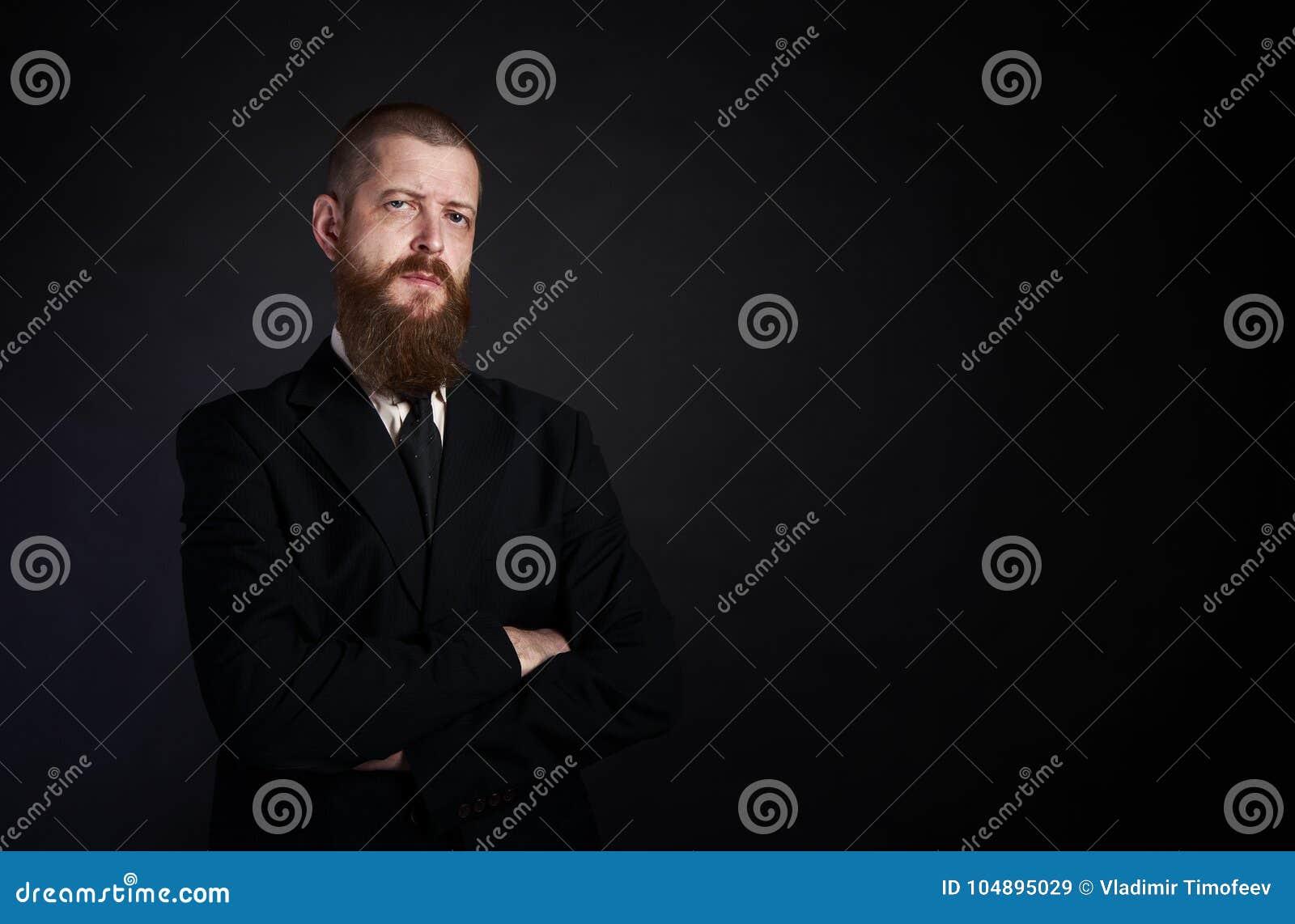 Бизнесмен с бородой на черной предпосылке в черном месте костюма для экземпляр-затира