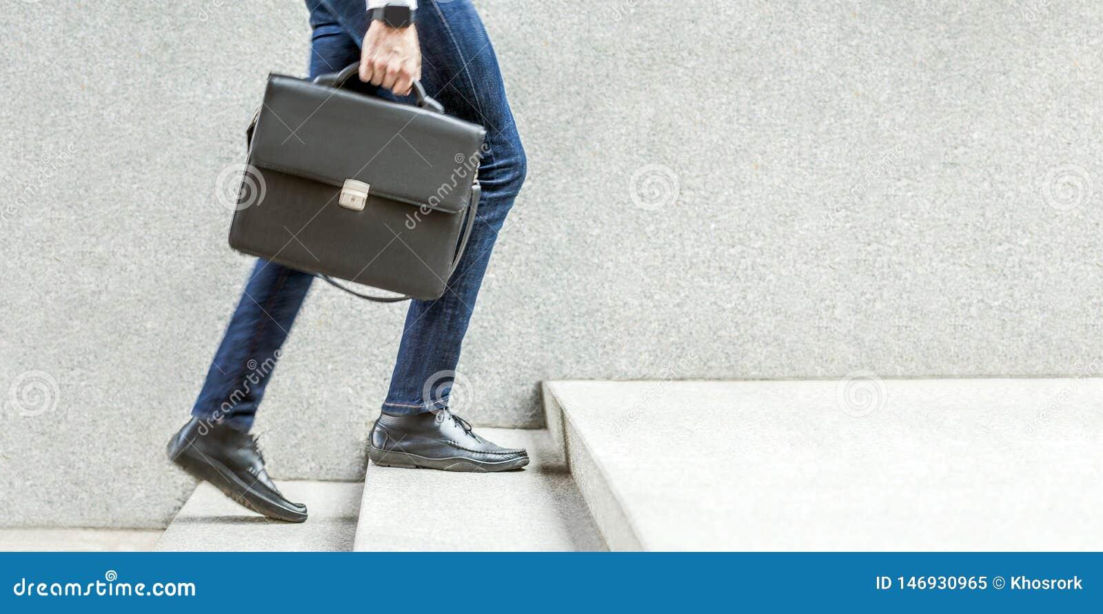 Бизнесмен с черным портфелем в руке идя вверх на лестницы