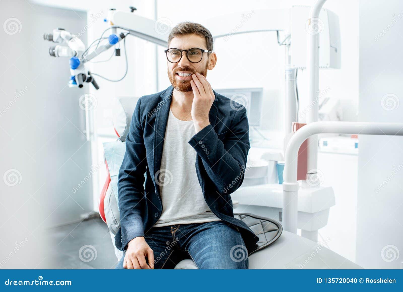 Бизнесмен с toothache в зубоврачебном офисе