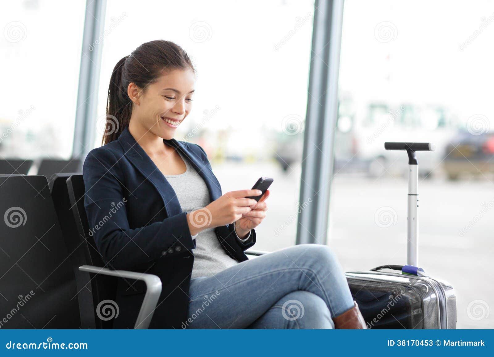 Бизнес-леди авиапорта на умном телефоне на стробе