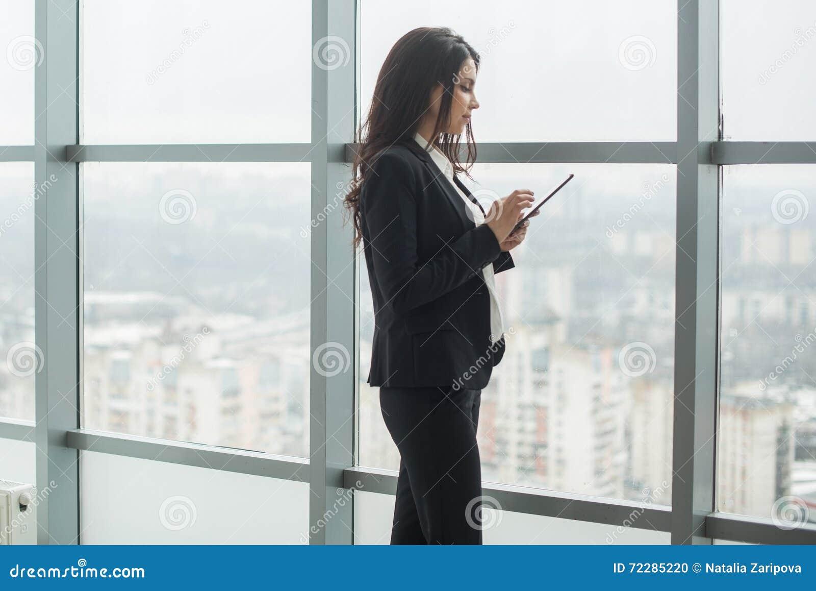 Download Бизнес-леди стоя на окне с таблеткой Стоковое Фото - изображение насчитывающей женщина, lifestyle: 72285220