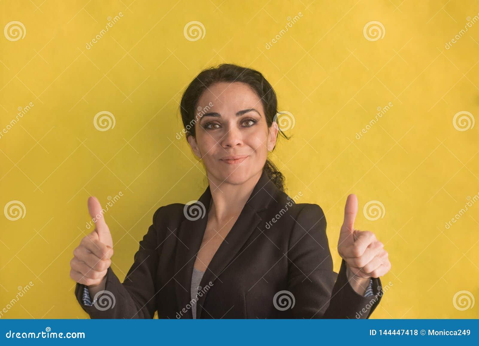 Бизнес-леди брюнета над предпосылкой делая счастливые большие пальцы руки вверх