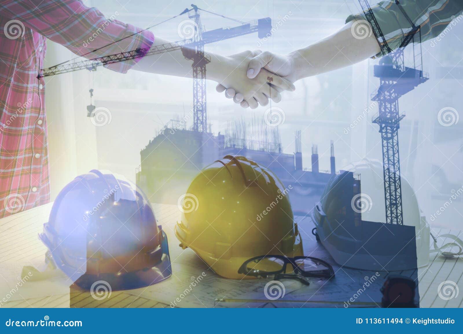 Бизнес-леди и рукопожатие инженера работая бизнесменов