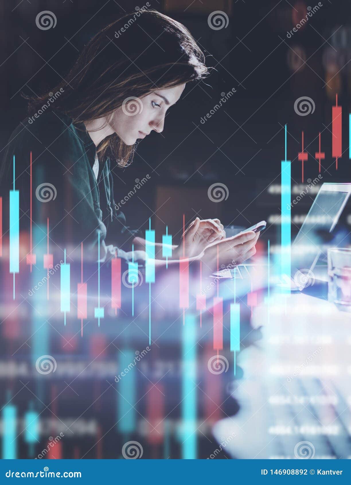 Бизнес-леди работая вечером офис в переднем ноутбуке с финансовыми диаграммами и статистикой на мониторе Двойник
