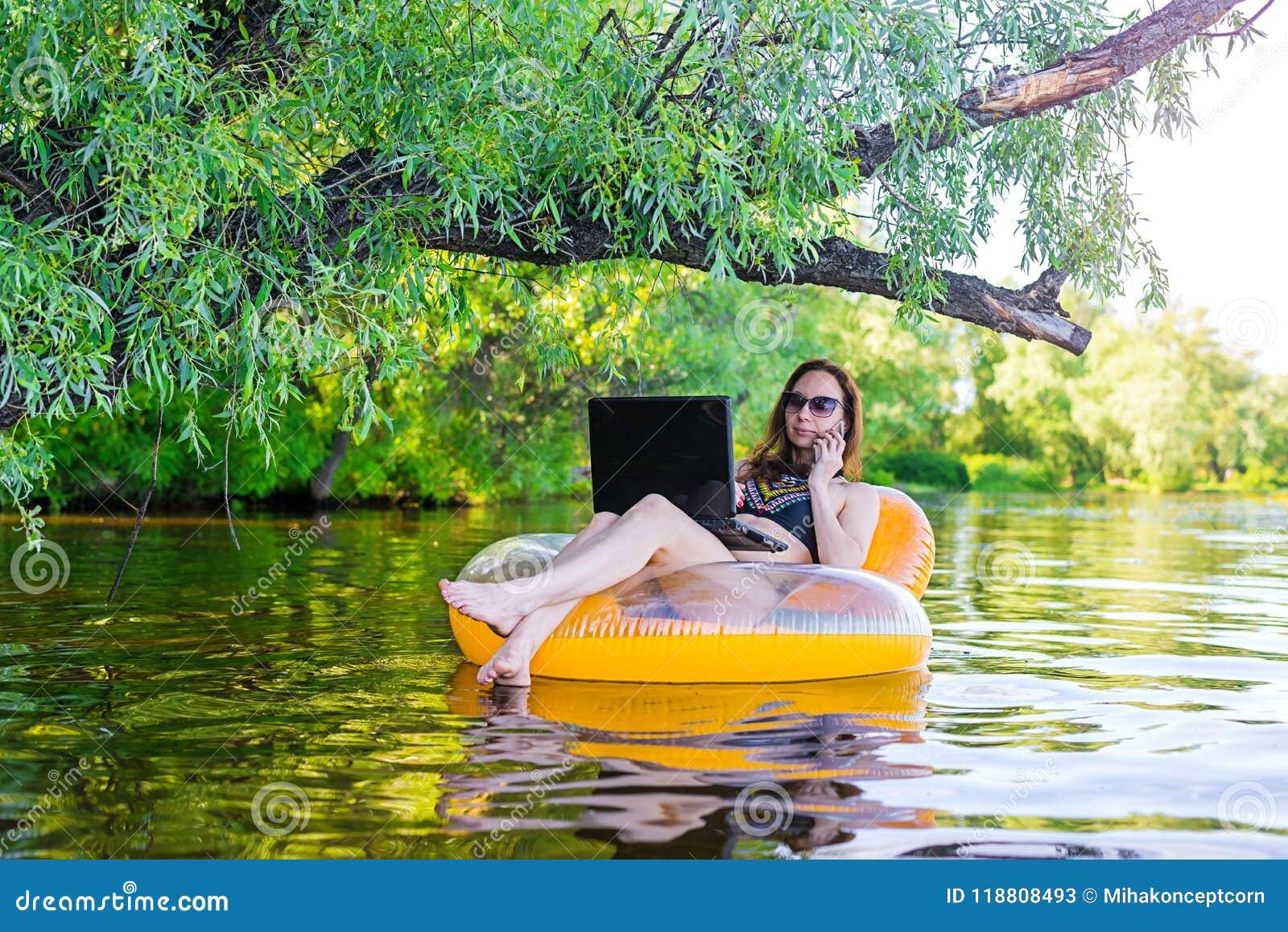 Бизнес-леди работая на компьтер-книжке и говоря на smartphone в раздувном кольце в воде, экземпляре открытого космоса