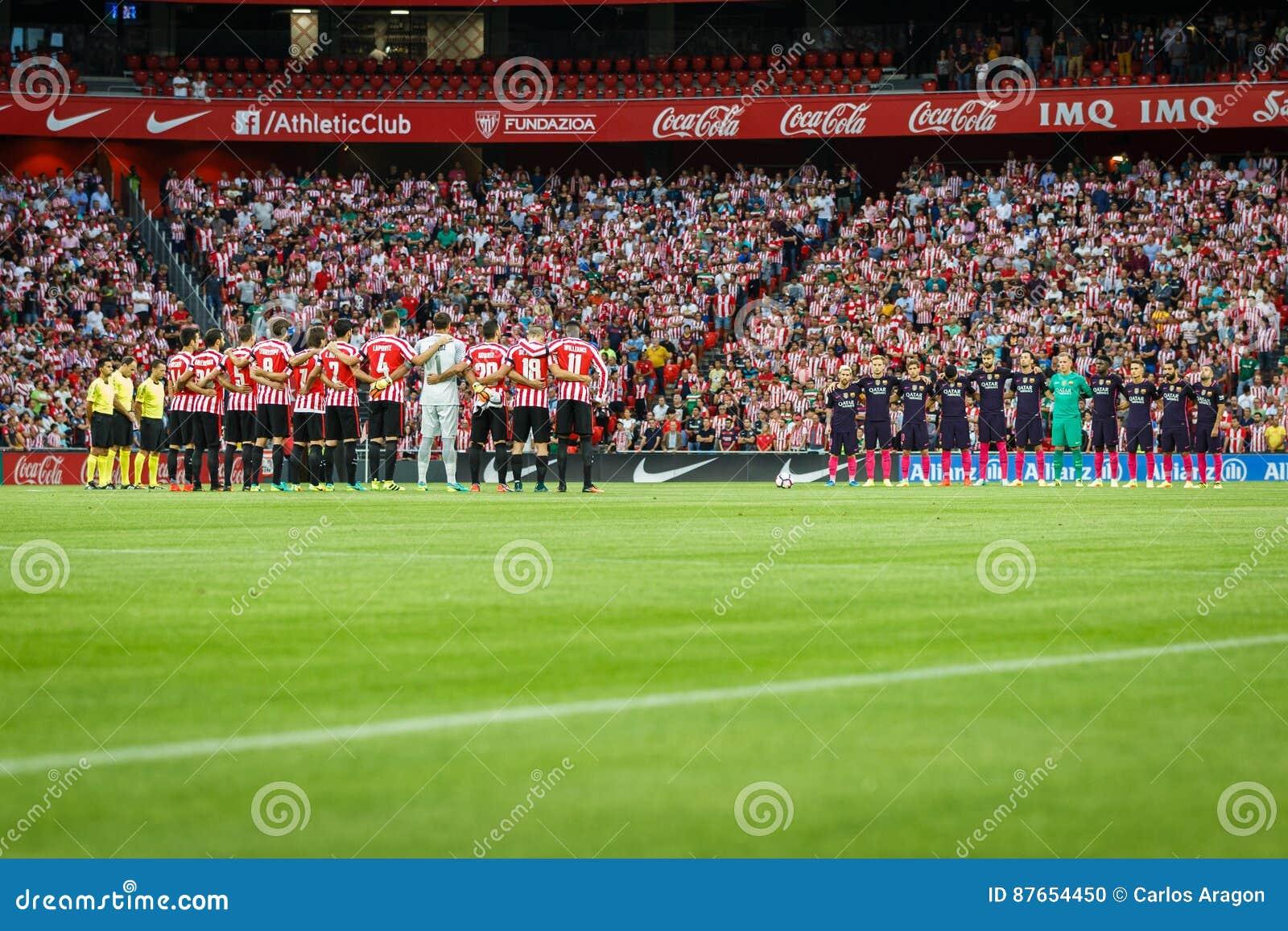 БИЛЬБАО, ИСПАНИЯ - 28-ОЕ АВГУСТА: 2 команды прижались во время минуты безмолвия в спичке между атлетическим Бильбао и FC Barcelon