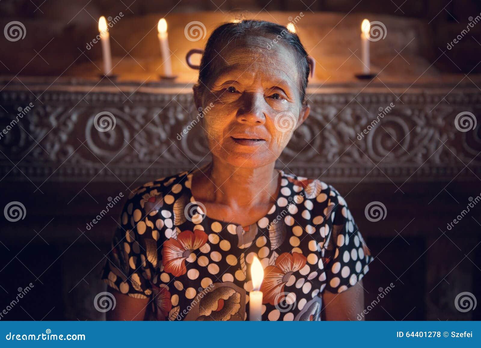 Бирманский свет горящей свечи prayingwith женщины