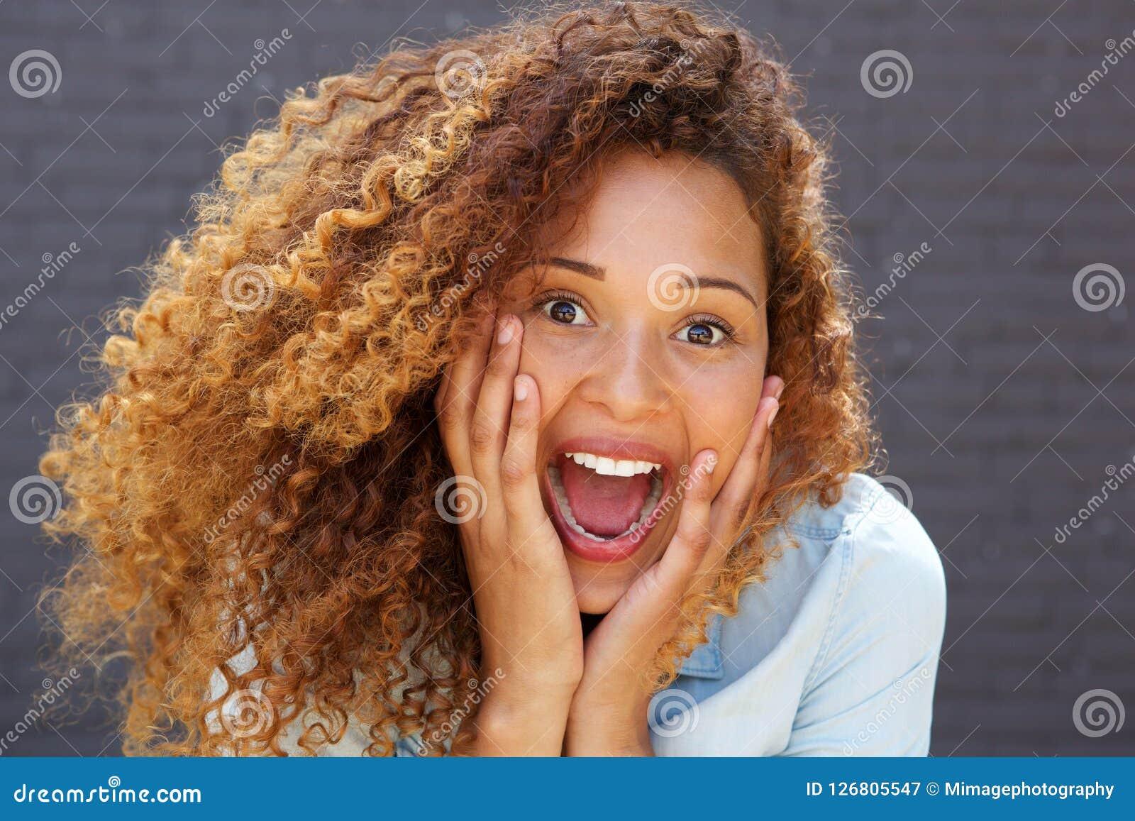 Близкая поднимающая вверх молодая женщина с удивленным выражением стороны