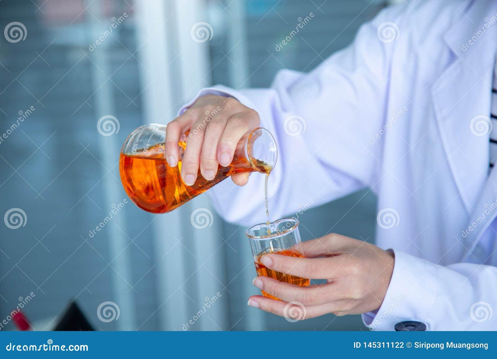 Близкая поднимающая вверх рука ученого лить оранжевую жидкость
