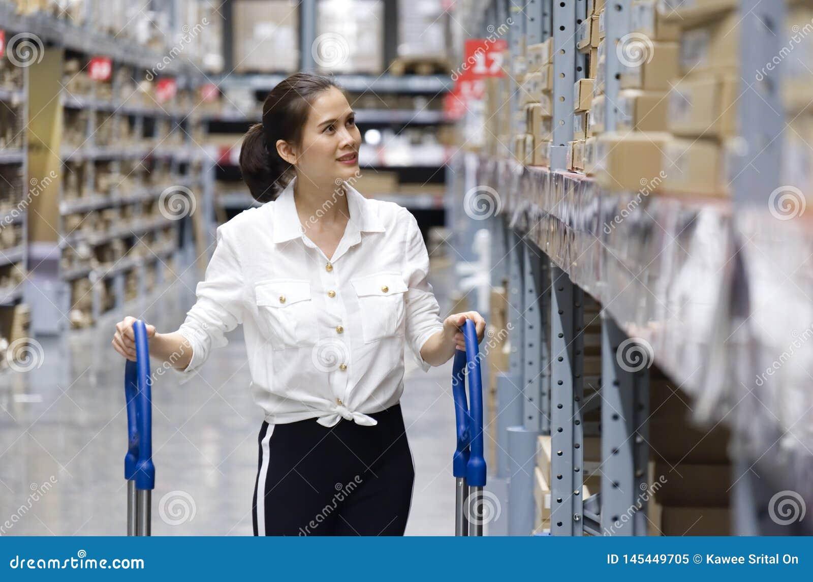 Близкая поднимающая вверх съемка азиатского милого клиента ища продукты в складе магазина Девушка нажимая тележку и найти товары