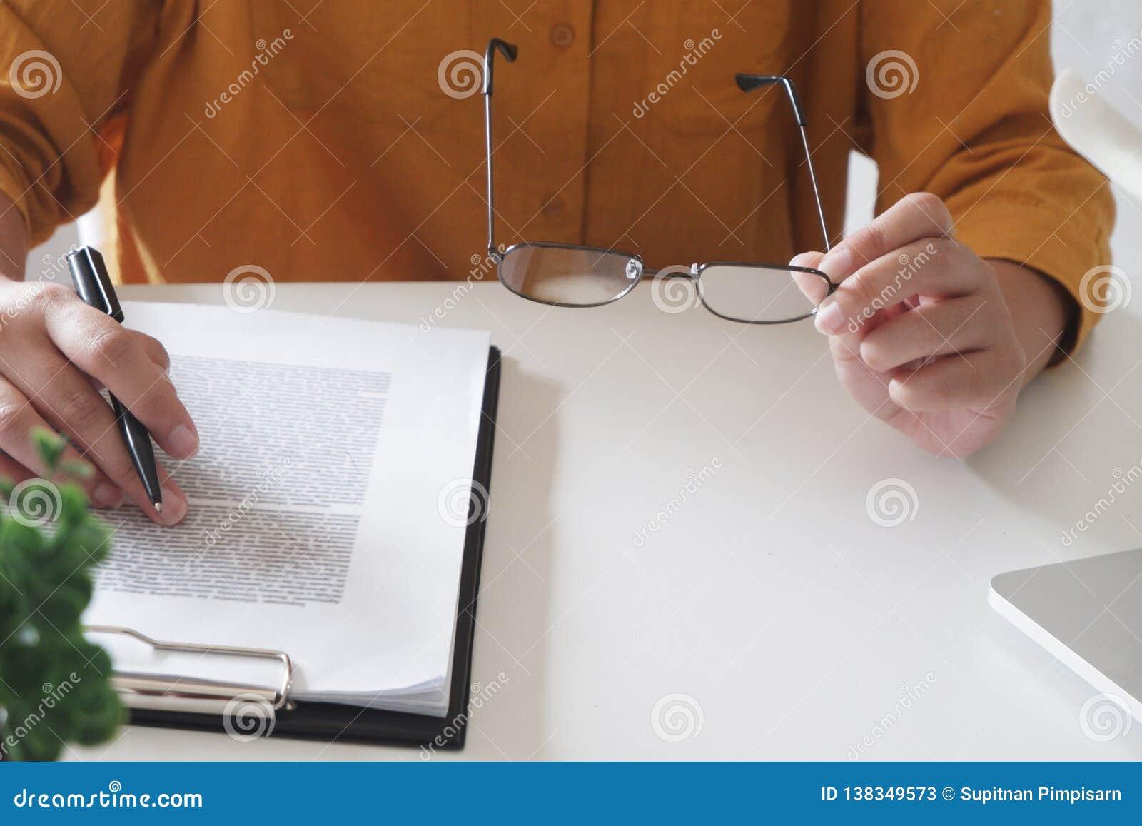 близкие женские руки вверх пишущ что-то и удержание стекел в ее офисе