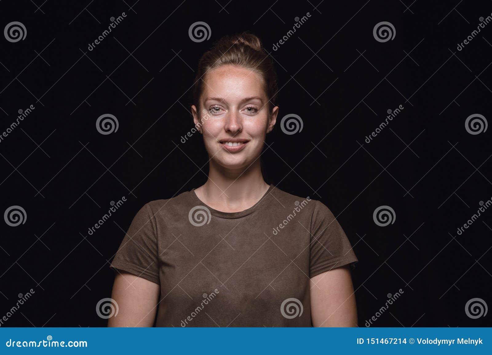 Близкий поднимающий вверх портрет молодой женщины изолированный на черной предпосылке студии