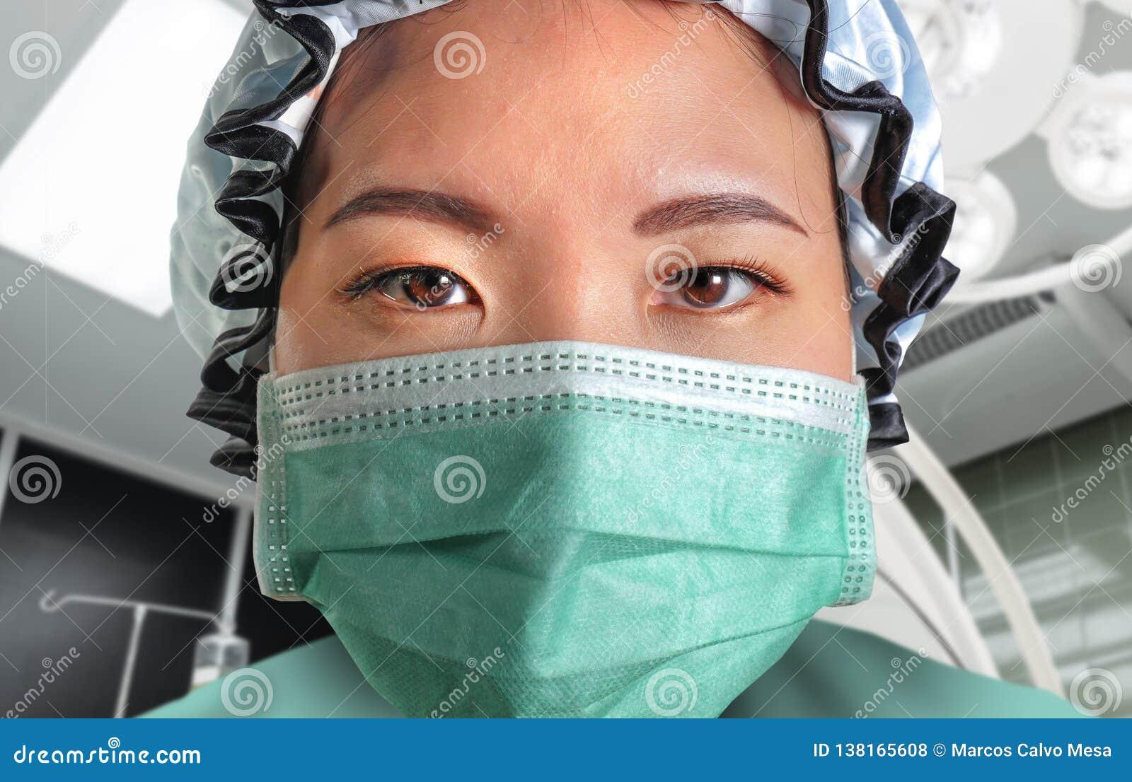 Близкий поднимающий вверх портрет молодой привлекательной и уверенной азиатской корейской женщины доктора медицины в защитном лиц