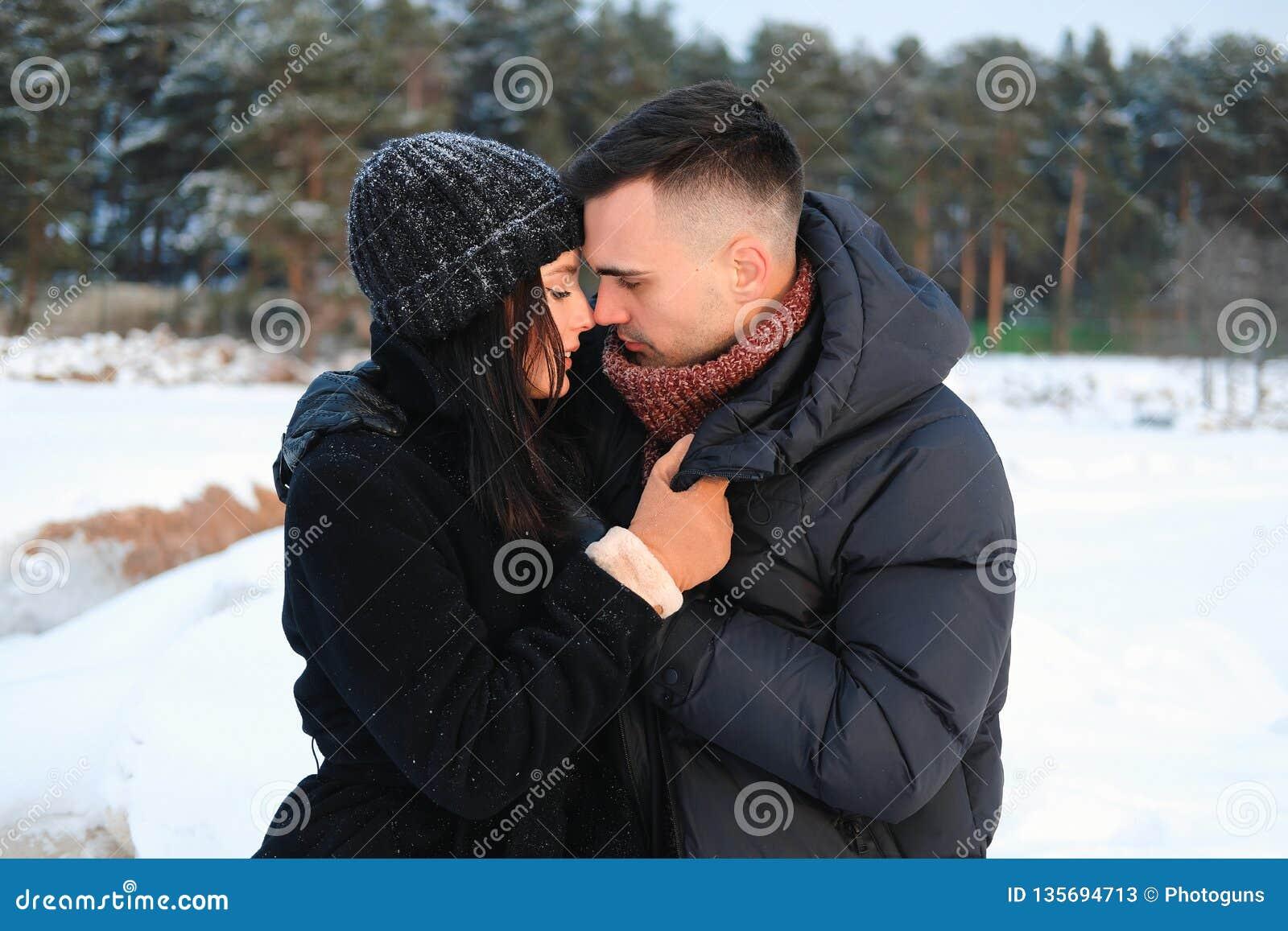 Близкий поднимающий вверх портрет молодых привлекательных пар в обнимать любов на открытом воздухе в парке зимы Чувственное нежно
