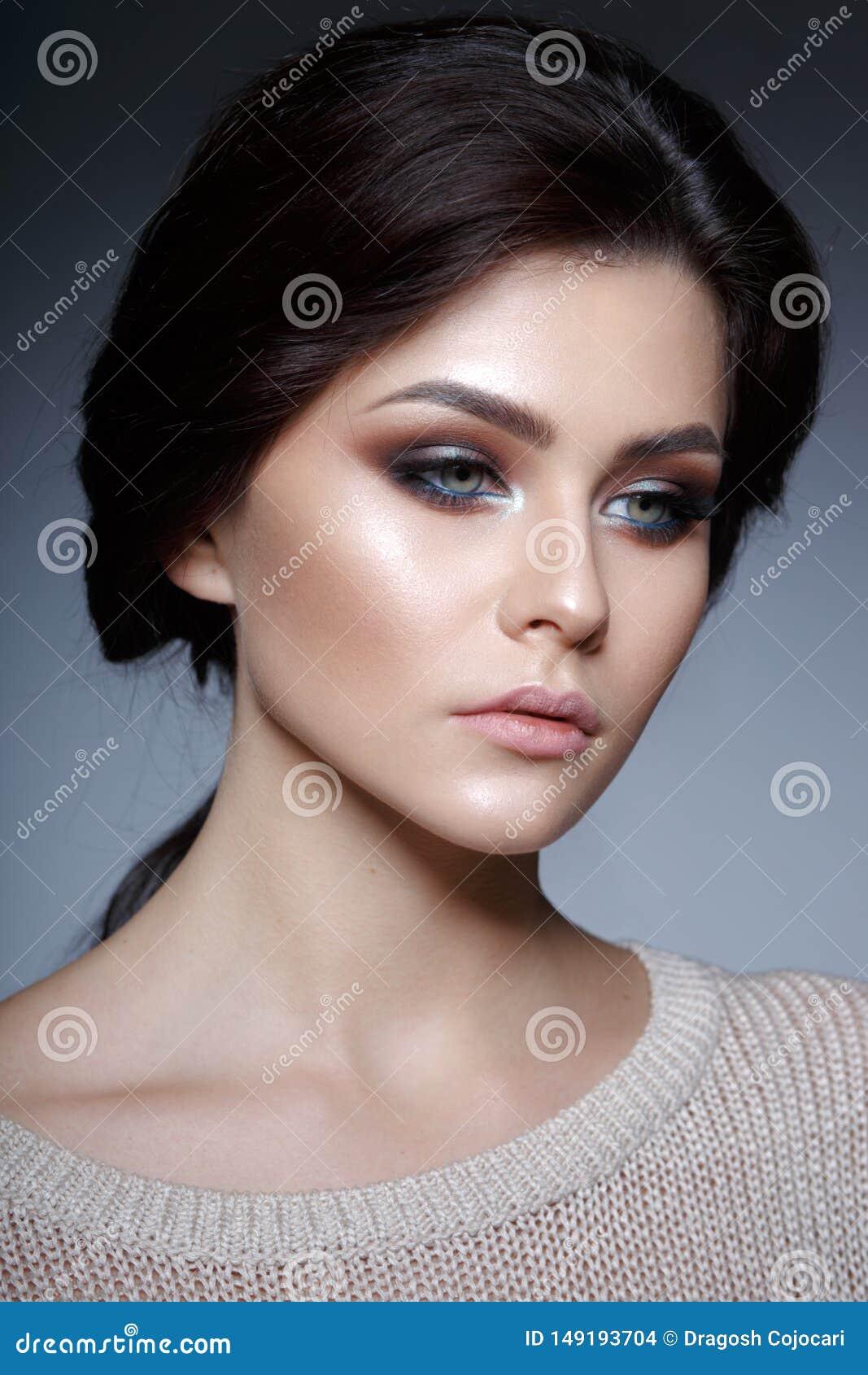 Близкий поднимающий вверх портрет профиля грациозной молодой женщины с идеальным макияжем и свежей кожей, на серой предпосылке