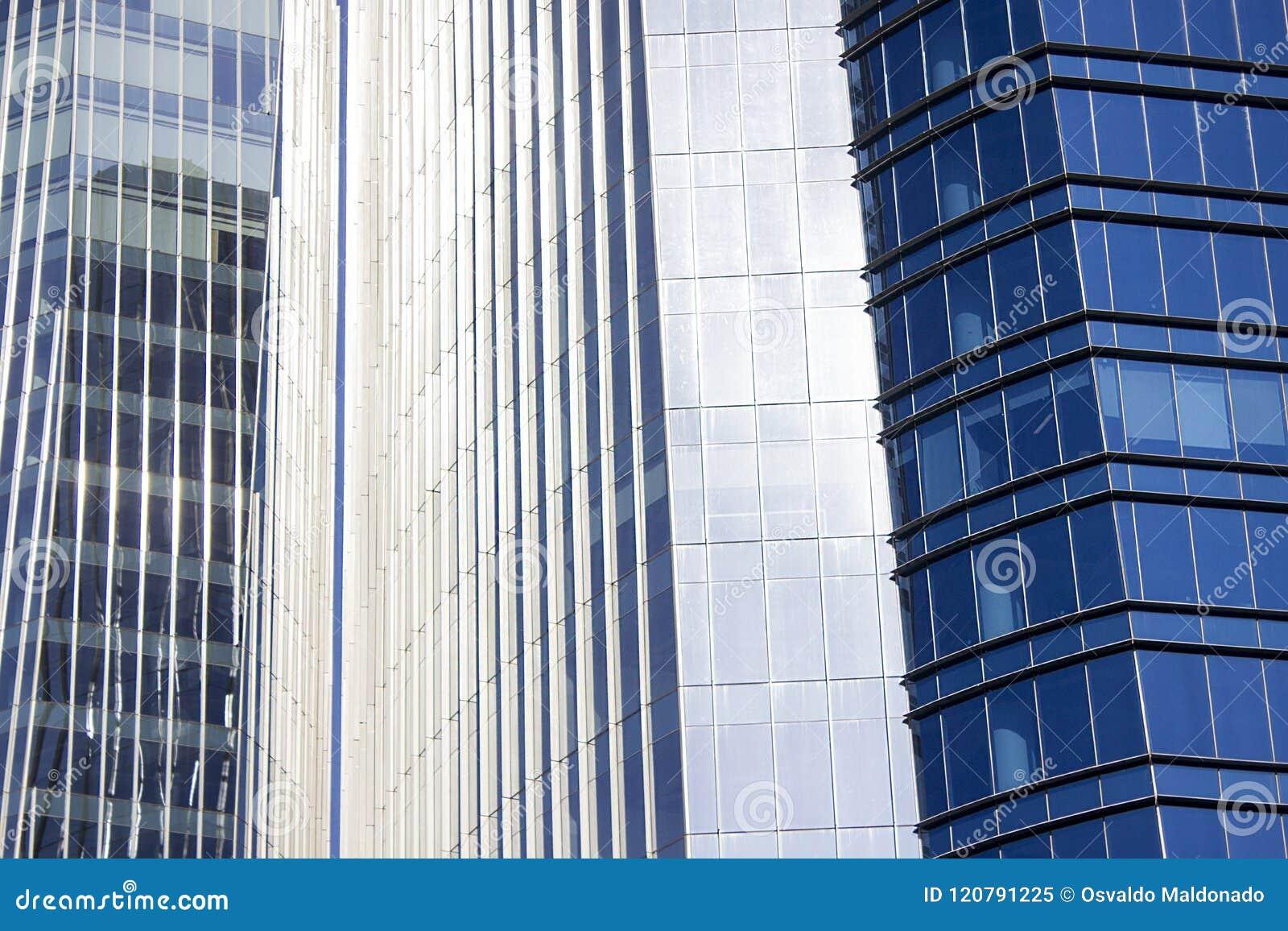 Близкий снимок пары офисных зданий близнецов корпоративных голубых с striped дизайном