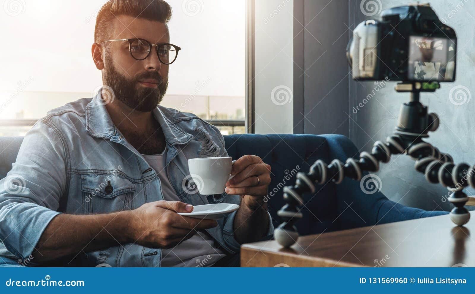 Блоггер бородатого человека видео- в стильных стеклах снимает видео- течь для потребителей пока сидящ в кафе и выпивая кофе