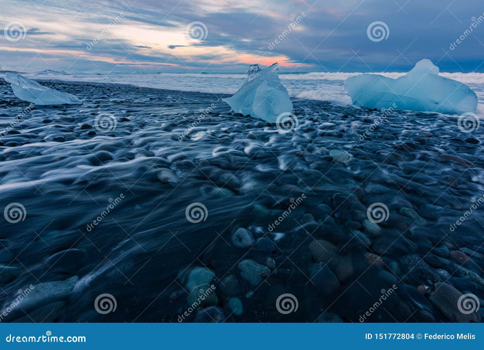 Блоки льда на пляже отработанной формовочной смеси во время захода солнца в Исландии