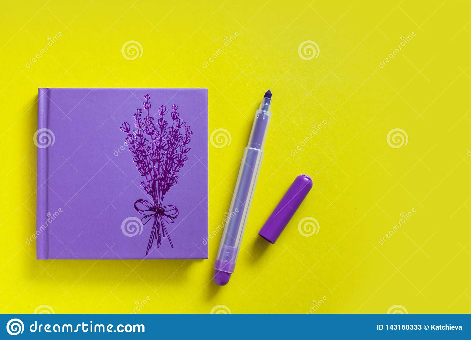 Блокнот сирени с ручкой войлока на желтой предпосылке