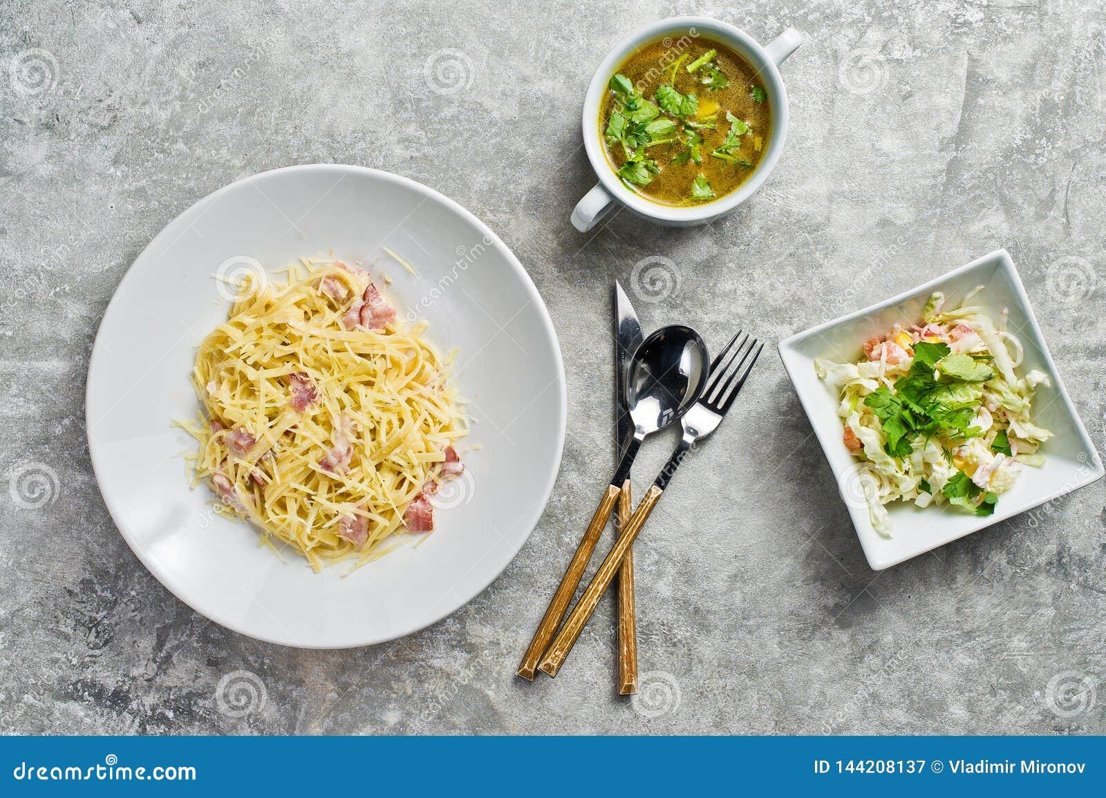 3 блюда в ресторане, макаронных изделиях Carbonara, зеленом салате и курином супе