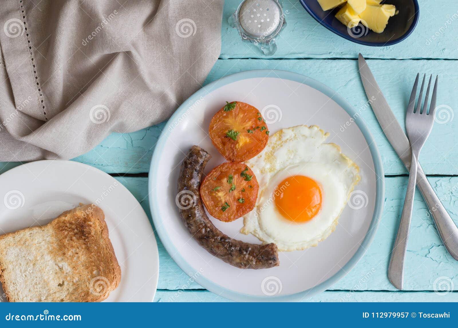 Блюдо завтрака с яичницей, сосиской, томатом и здравицей Overhe
