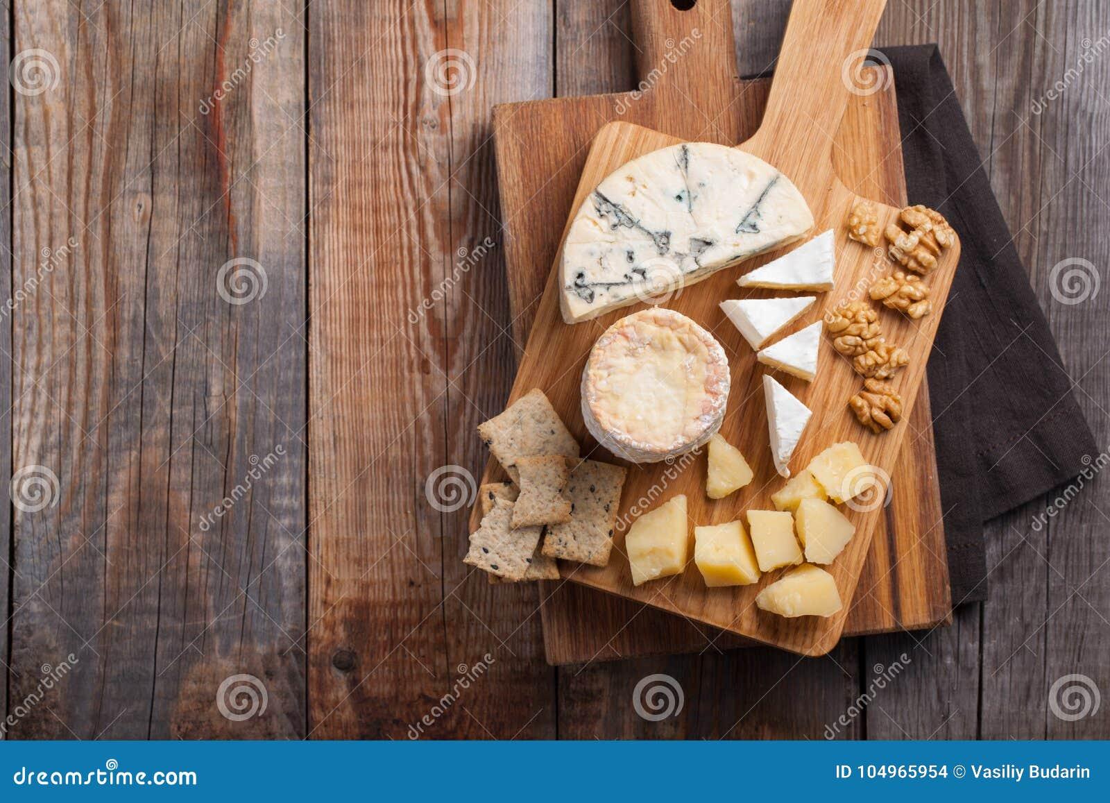 Блюдо сыра дегустации на деревянной плите Еда для вина и романтичное, деликатес сыра на деревянной деревенской таблице Взгляд све