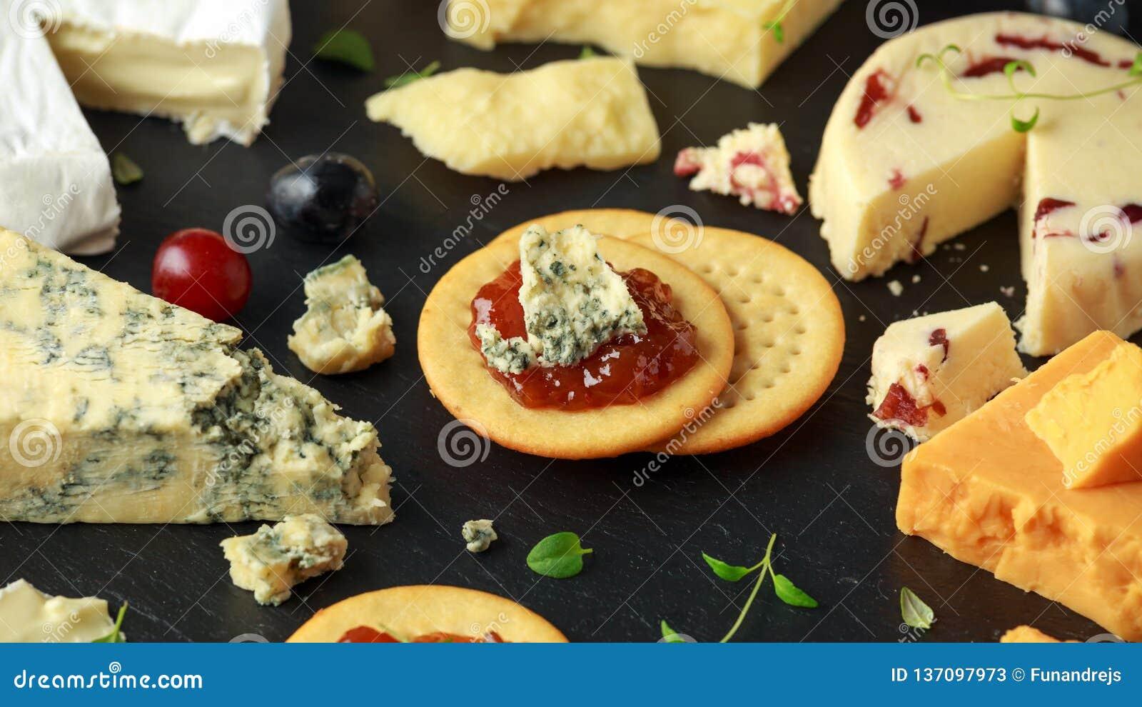 Блюдо сыров, который служат с виноградинами, чатни эля, мед, шутихи на каменной доске Бри, чеддер, красный Лестер