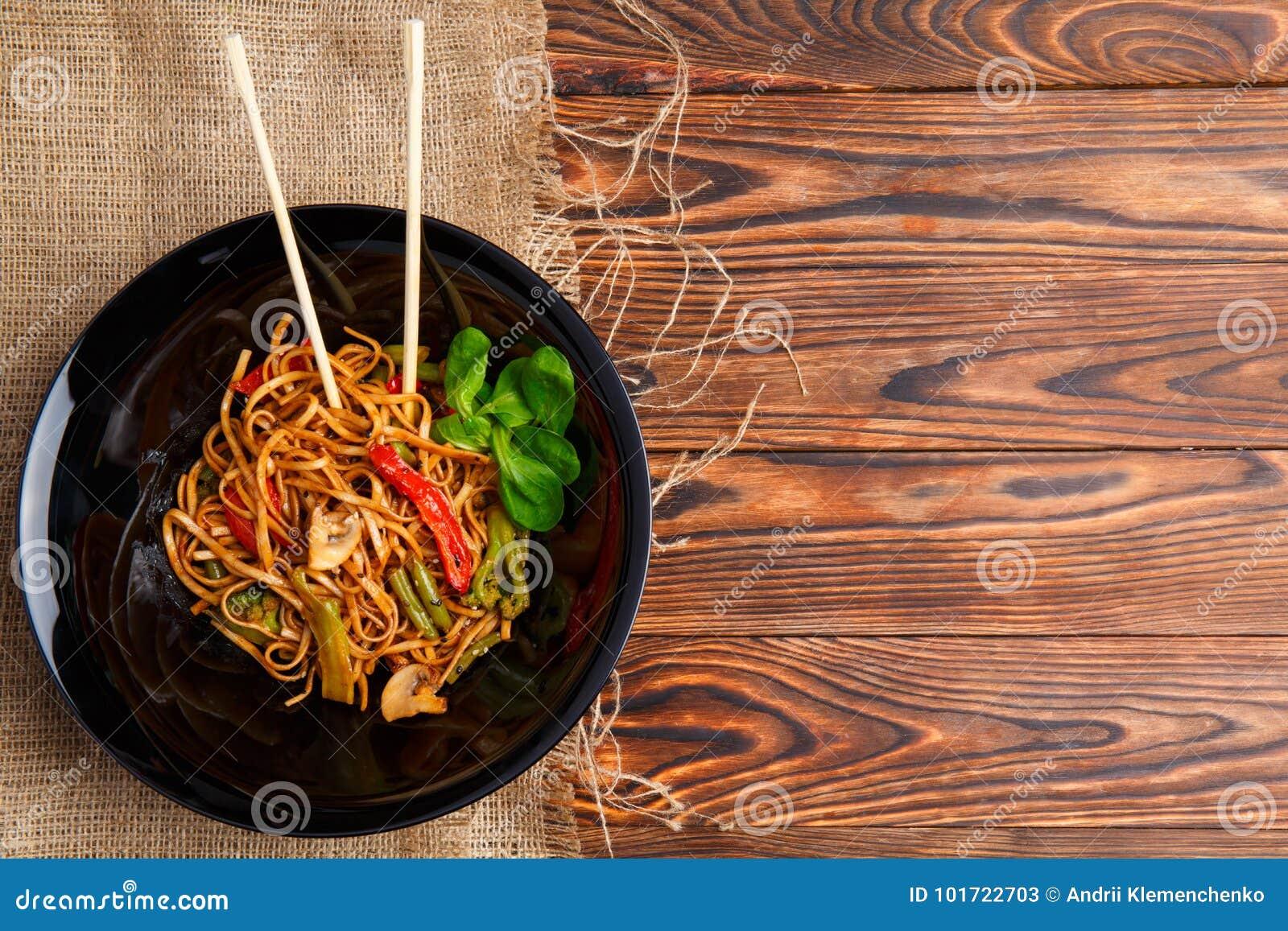 Блюдо традиционного китайския на круглой плите, лапшах риса, капусте или зеленой капусте и зажаренных овощах