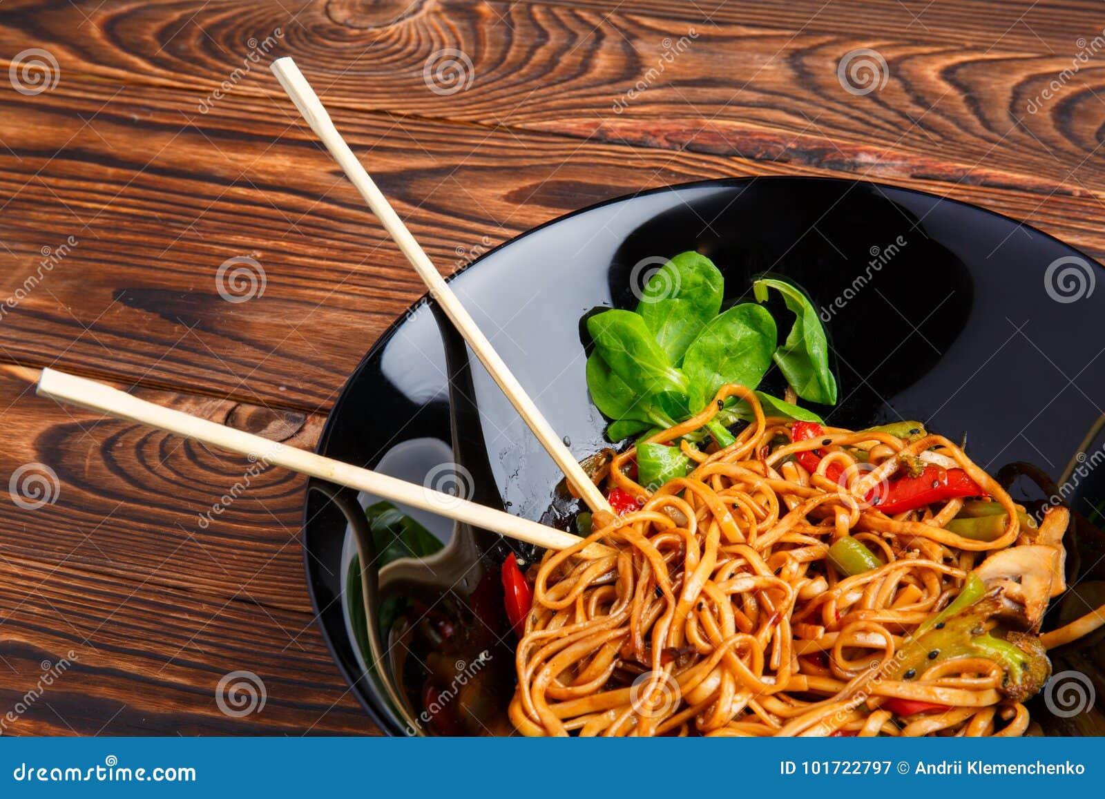 Блюдо традиционного китайския на круглой плите, лапшах риса, капусте капусты зеленой и зажаренных овощах